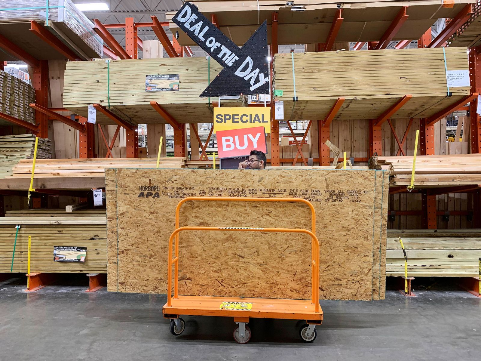 A shopper stands with a dolly of plywood at The Home Depot ahead of Hurricane Dorian on Thursday, Aug. 29, 2019, in Pembroke Pines, Fla. (AP Photo/Brynn Anderson)