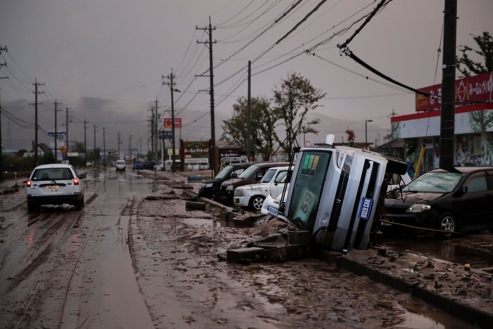 Typhoon-damaged cars sit on the street covered with mud Monday, Oct. 14, 2019, in Hoyasu, Japan. . (AP Photo/Jae C. Hong)
