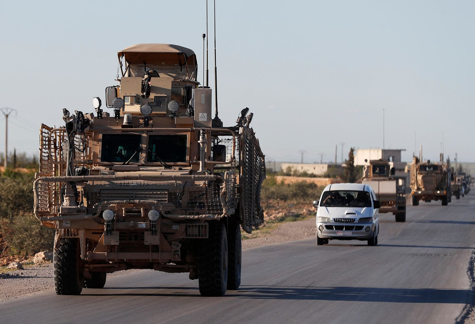 FILE - In this Saturday, March 31, 2018 file photo, a convoy of U.S. troops drive along a road leading to the front line with Turkish-backed fighters, in Manbij, north Syria. (AP Photo/Hussein Malla, File)