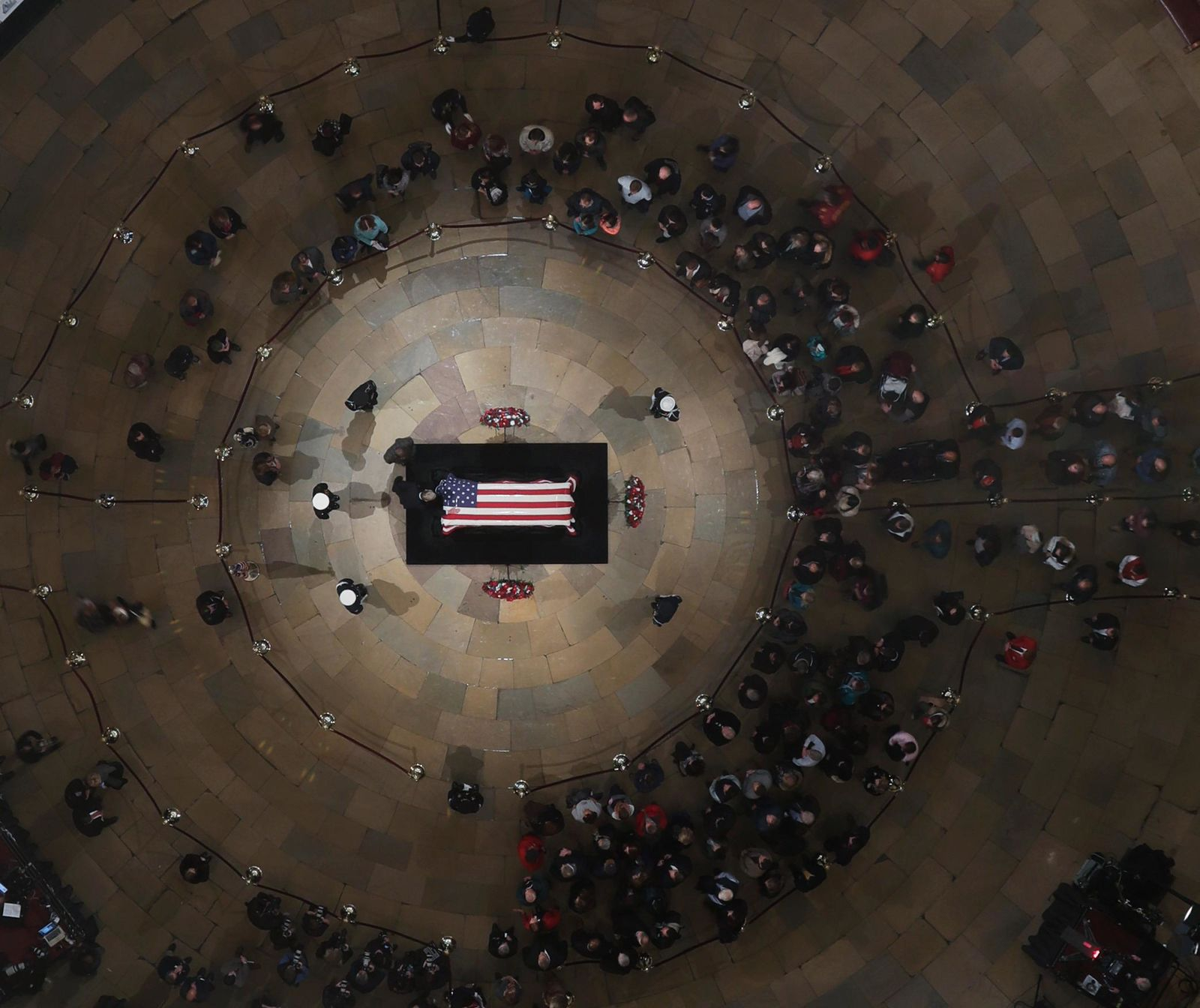 A mourner puts a hand on the flag-draped casket of former President George H. W. Bush as he lies in state in the U.S. Capitol Rotunda Tuesday, Dec. 4, 2018, in Washington. (Pool photo by Morry Gash via AP)