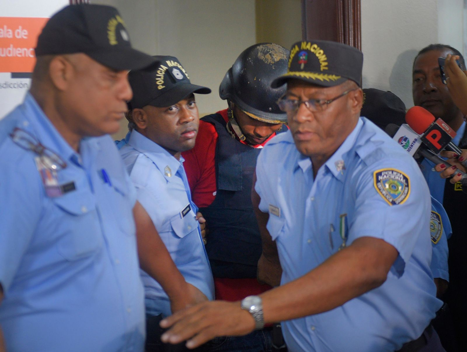 "Gabriel Alexander Pérez Vizcaino, alias ""Bone,"" behind wearing helmet, a suspect in the shooting of former Boston Red Sox slugger David Ortiz, is taken to court in Santo Domingo, Dominican Republic, Monday, June 17, 2019. Ortiz was shot in the back at a bar in the Dominican Republic on Sunday, June 9. (AP Photo/Roberto Guzman)"
