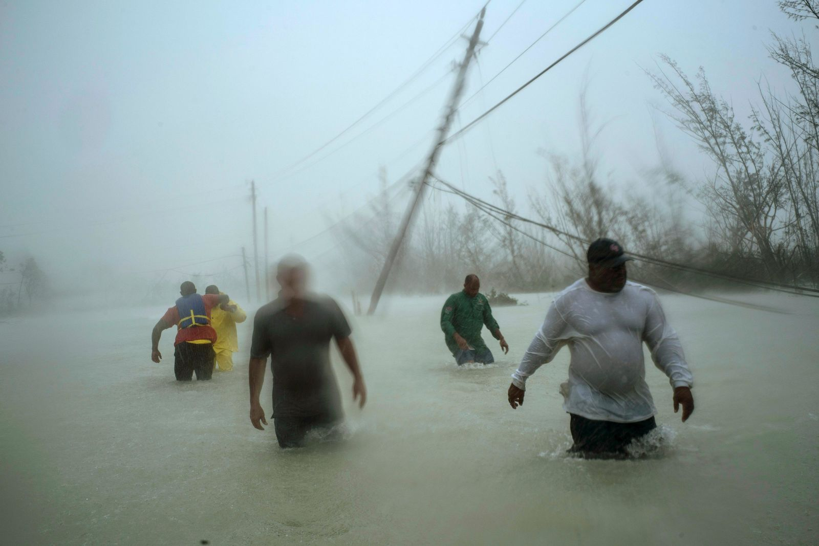 Volunteers walk under the wind and rain from Hurricane Dorian through a flooded road as they work to rescue families near the Causarina bridge in Freeport, Grand Bahama, Bahamas, Tuesday, Sept. 3, 2019. (AP Photo/Ramon Espinosa)