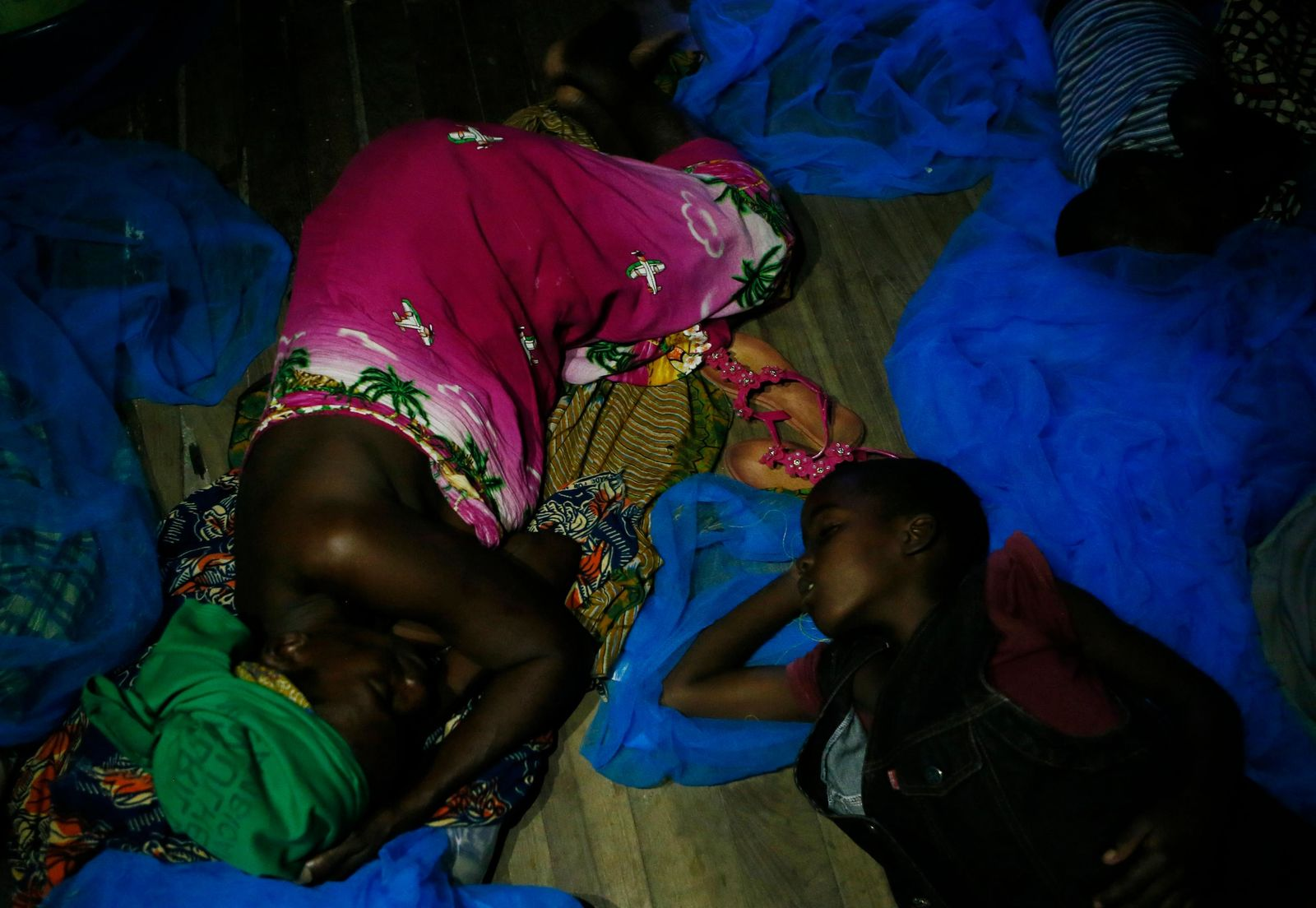 A displaced mother and child, victims of Cyclone Idai, sleep under a mosquito net at the Samora Machel Secondary School which is being used to house victims of the floods in Beira, Mozambique, Sunday March 24, 2019. (AP Photo/Phill Magakoe)