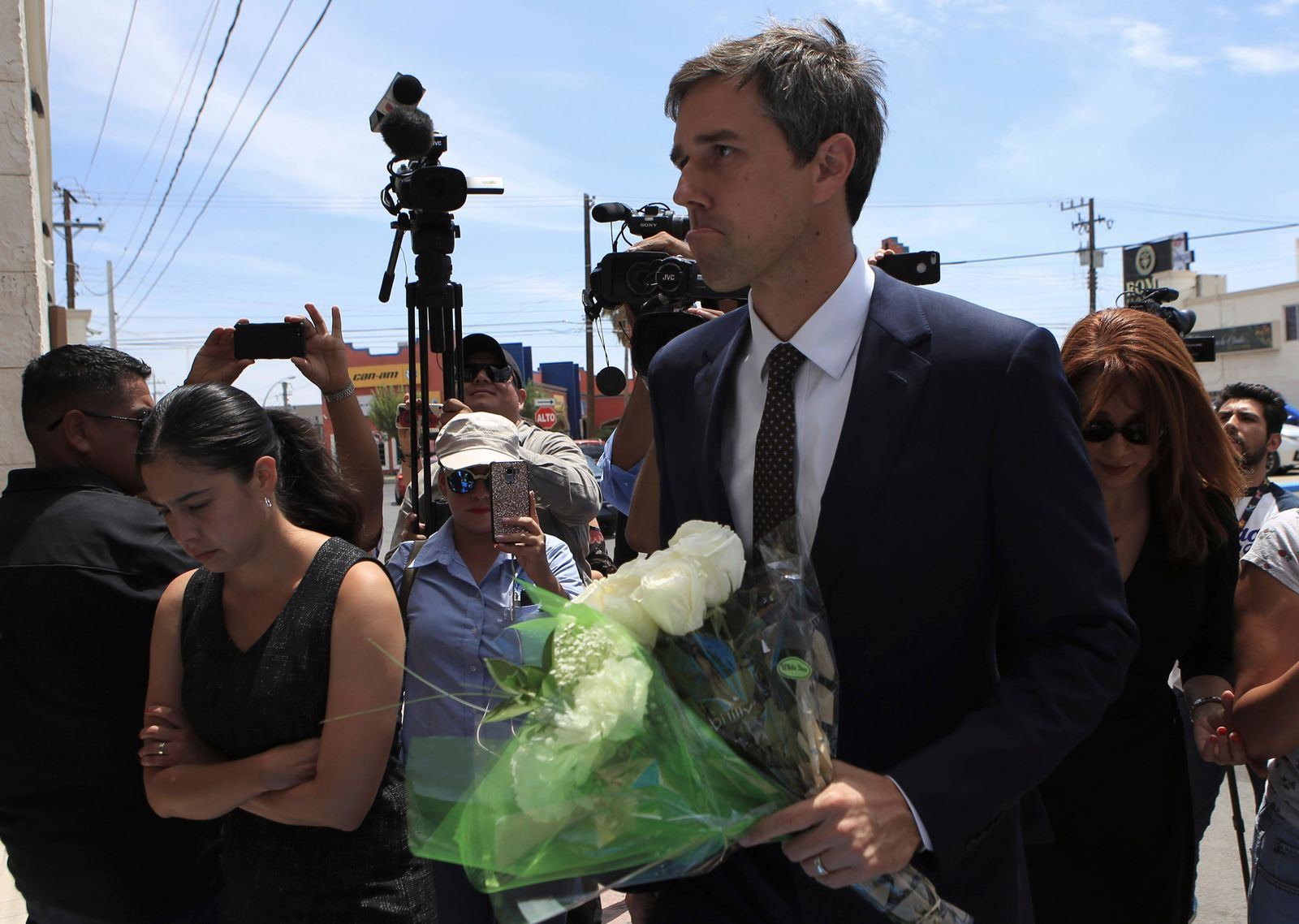 Democratic presidential candidate Beto O'Rourke arrives with flowers to the Perches funeral home in Ciudad Juarez, Mexico, Thursday, Aug. 8, 2019, to attend a service for Ivan Filiberto Manzano, one of the 22 people killed in a shooting at a Walmart in El Paso. (AP Photo/Christian Chavez)