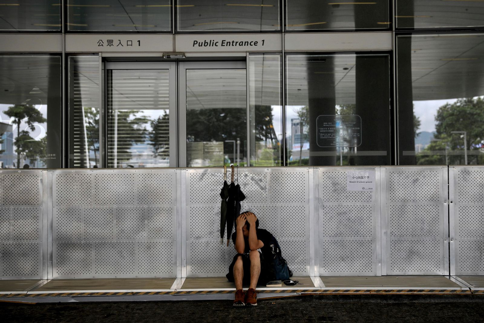 A protester takes a rest outside the Legislative Council in Hong Kong, Tuesday, June 18, 2019. Hong Kong's government headquarters reopened Tuesday as the number of protesters outside dwindled to a few dozen and life returned to normal in the former British colony. (AP Photo/Vincent Yu)