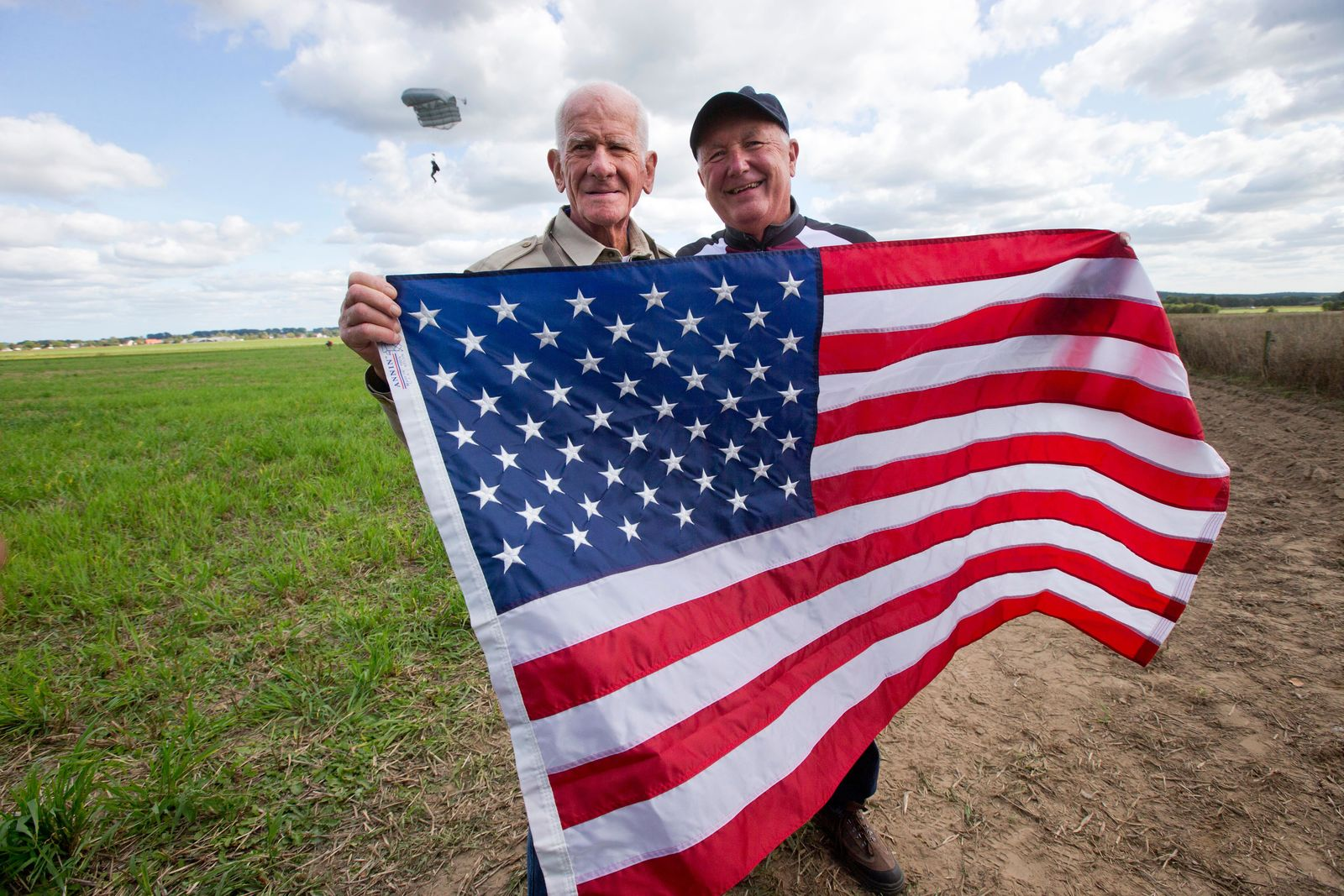 Tom Rice, a 98-year-old American WWII veteran, and U.S. Ambassador Pete Hoekstra, right, pose with the U.S. flag after landing with a tandem parachute jump from a plane near Groesbeek, Netherlands, Thursday, Sept. 19, 2019, as part of commemorations marking the 75th anniversary of Operation Market Garden. Rice jumped with the U.S. Army's 101st Airborne Division in Normandy, landing safely despite catching himself on the exit and a bullet striking his parachute. (AP Photo/Peter Dejong)