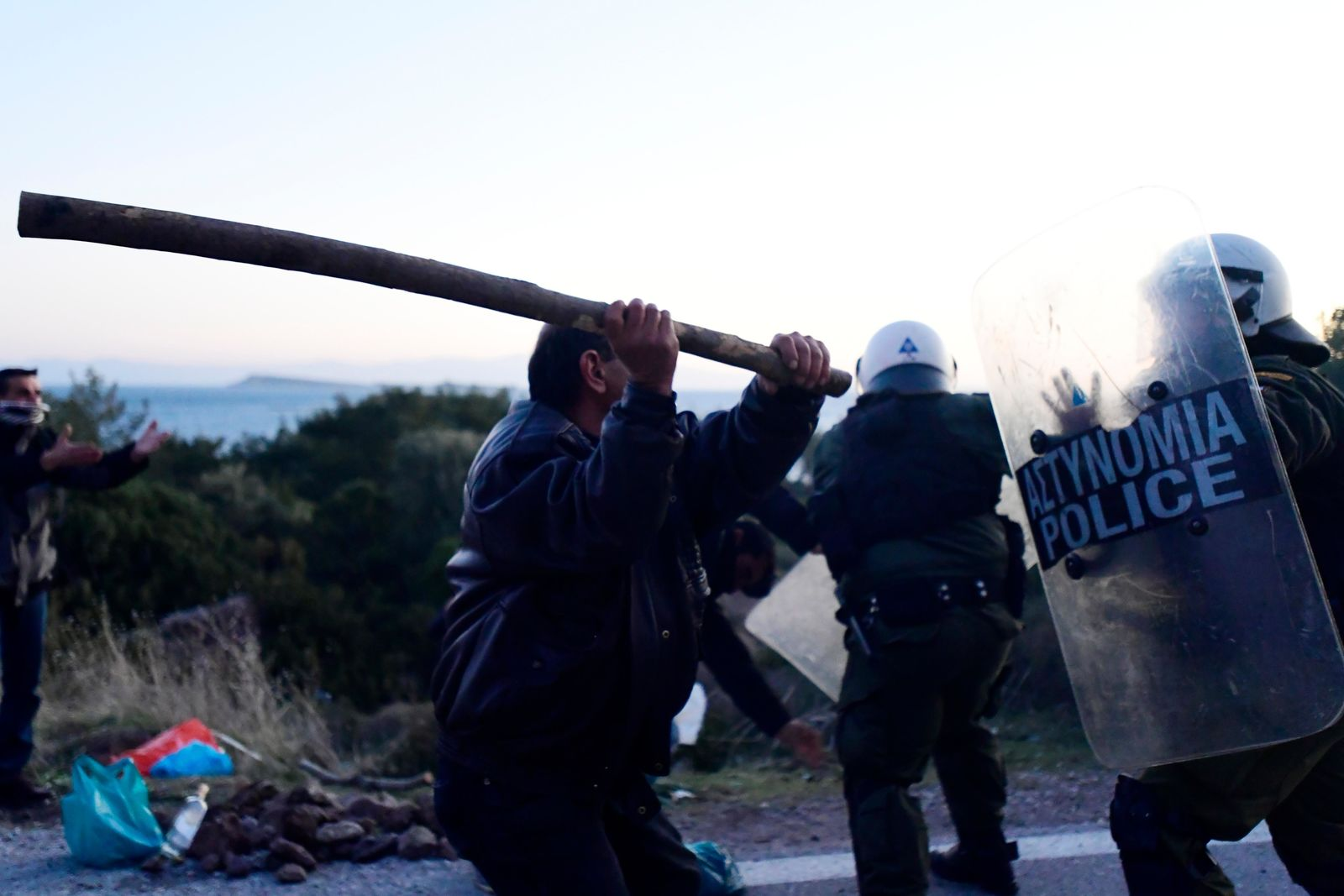 A local resident clashes with riot police at a roadblock in Karava village neat the area where the government plans to build a new migrant detention center, on the northeastern Aegean island of Lesbos, Greece, early Tuesday, Feb. 25, 2020. (AP Photo/Michael Varaklas)