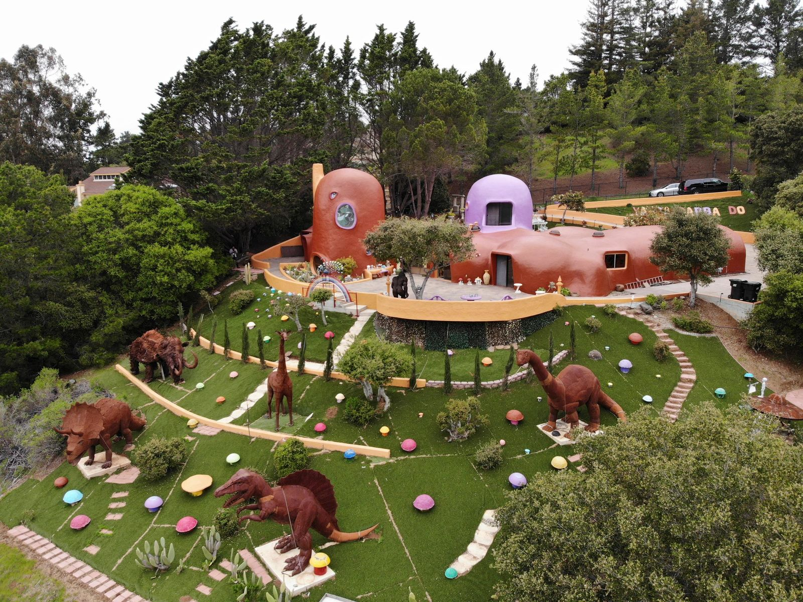 This Monday, April 1, 2019 photo, shows an aerial view of the Flintstone House in Hillsborough, Calif. The San Francisco Bay Area suburb of Hillsborough is suing the owner of the house, saying that she installed dangerous steps, dinosaurs and other Flintstone-era figurines without necessary permits. The owner and her attorney say they will fight for the rights of property owners and Fred and Barney fans everywhere. (AP Photo/Terry Chea)