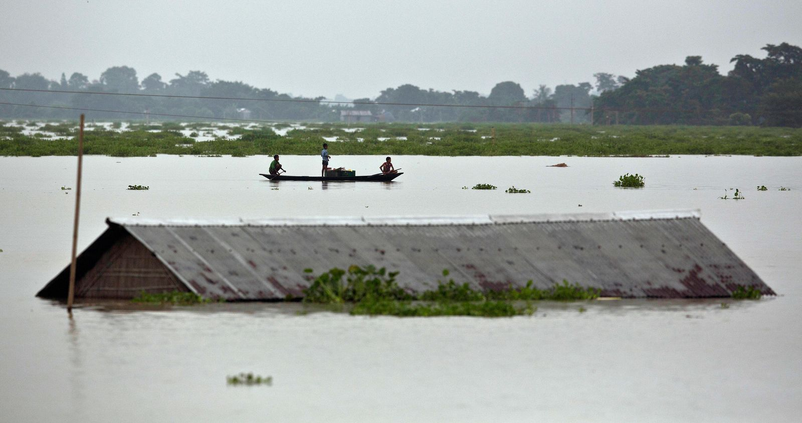 Flood affected villagers row near a submerged house in the flood water in Burha Burhi village east of Gauhati India, Monday, July 15, 2019. (AP Photo/Anupam Nath)