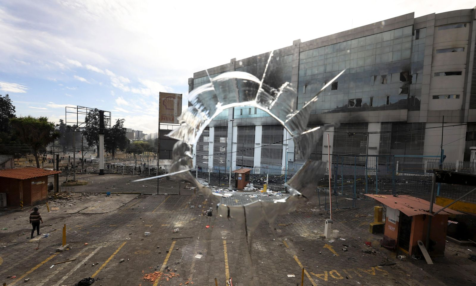 Photographed through a broken window, the national auditor's office stands across the street, damaged after it was attacked by anti-government protesters in Quito, Ecuador, Sunday, Oct. 13, 2019. (AP Photo/Fernando Vergara)