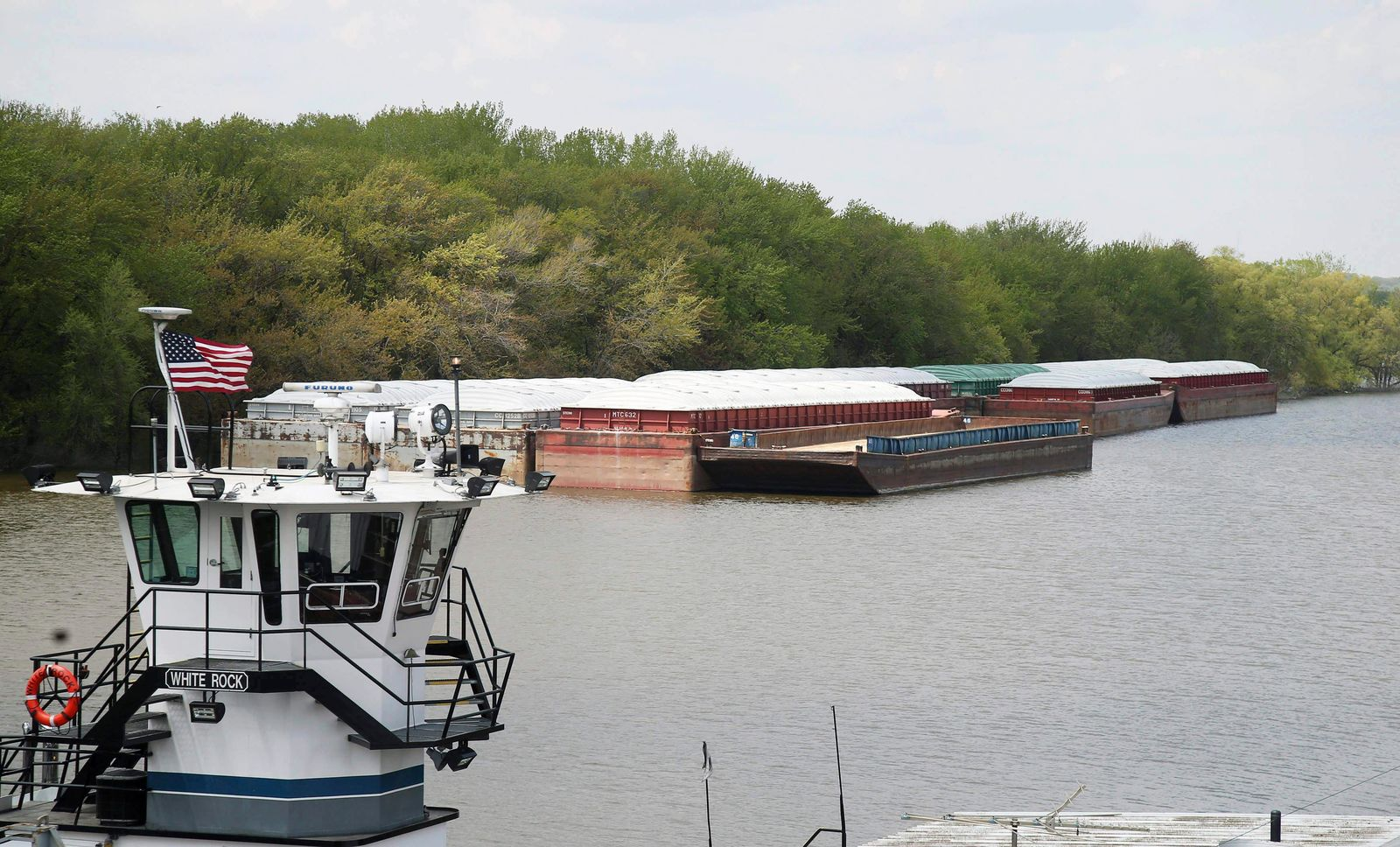 In this Tuesday, May 14, 2019 photo, empty barges are moored on the Mississippi River in St. Paul, Minn., as spring flooding interrupts shipments on the river. (AP Photo/Jim Mone)
