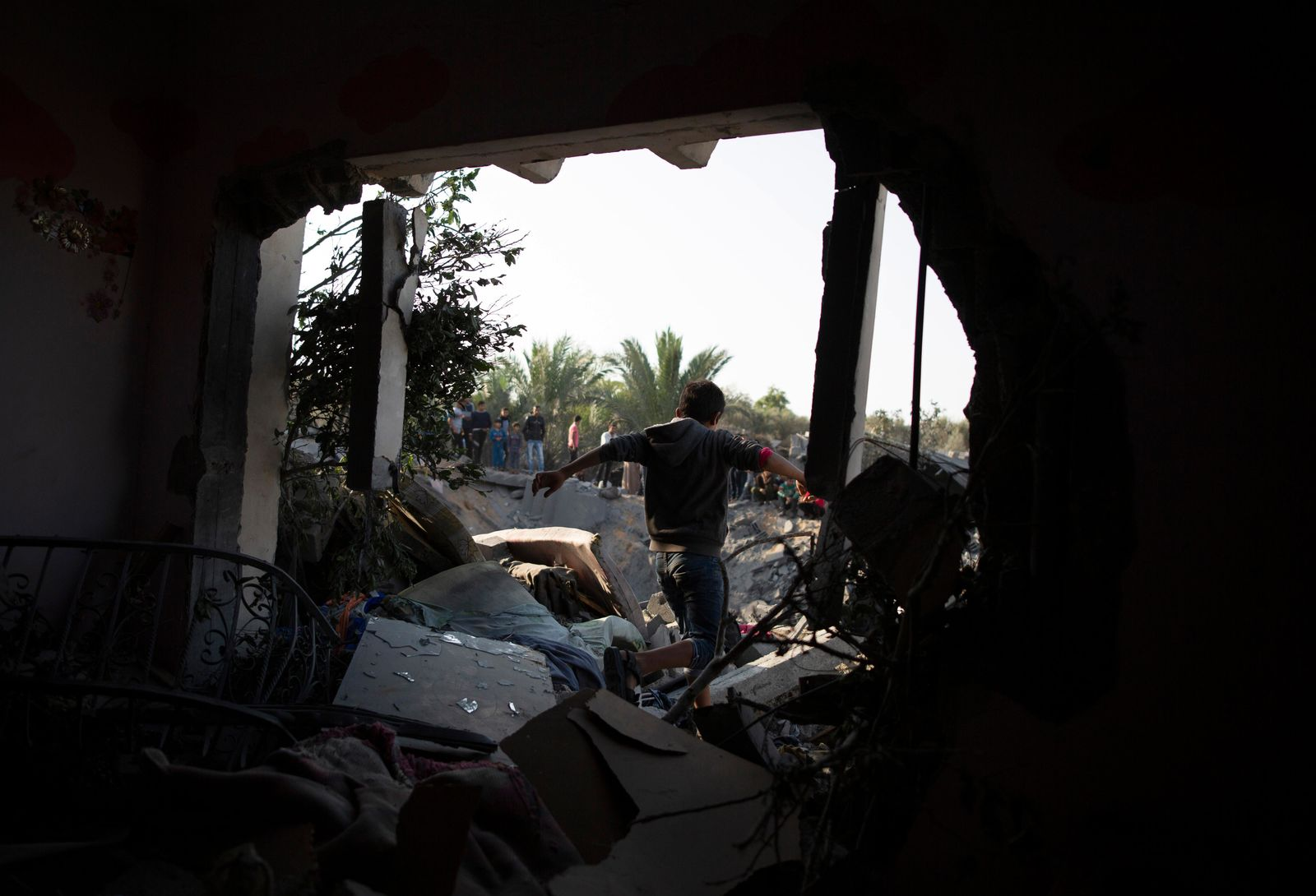 A Palestinian boy walks through a hole in a wall of a destroyed house following overnight Israeli missile strikes, in the town of Khan Younis, southern Gaza Strip, Thursday, Nov. 14, 2019. (AP Photo/Khalil Hamra)