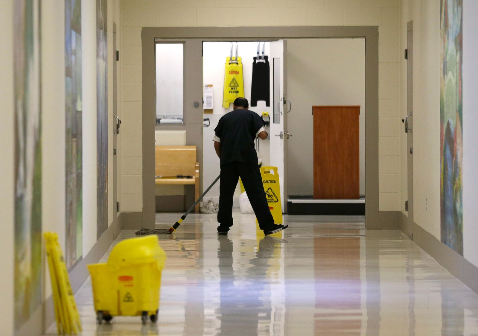 FILE - In this June 21, 2017, file photo, a detainee mops a floor in a hallway of the Northwest Detention Center in Tacoma, Wash., during a media tour of the facility.  The Trump administration is opposing Washington state's effort to make a privately run, for-profit immigration jail pay detainees minimum wage for the work they do. Washington Attorney General Bob Ferguson sued The GEO Group in 2017, saying its Northwest Detention Center in Tacoma must pay the state minimum wage to detainees who perform kitchen, janitorial and other tasks. (AP Photo/Ted S. Warren, File)