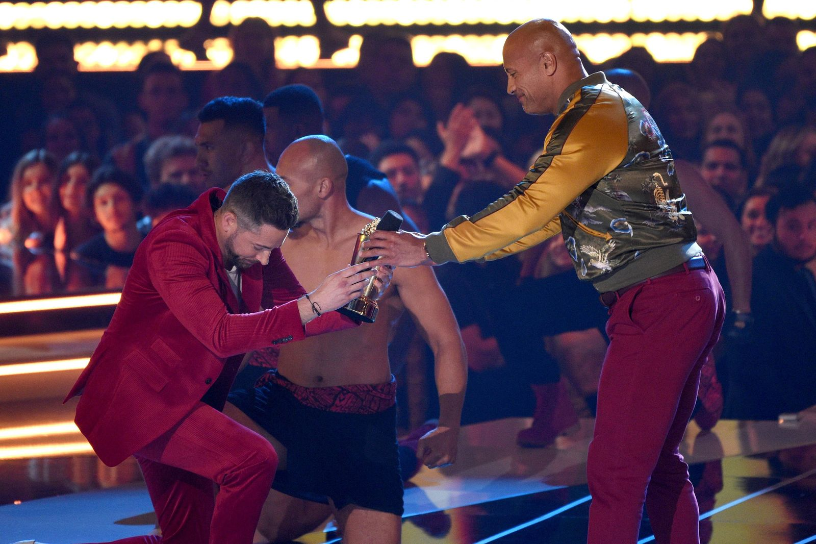 Zachary Levi bows as he presents the generation award to Dwayne Johnson, also known as The Rock, at the MTV Movie and TV Awards on Saturday, June 15, 2019, at the Barker Hangar in Santa Monica, Calif. (Photo by Chris Pizzello/Invision/AP)
