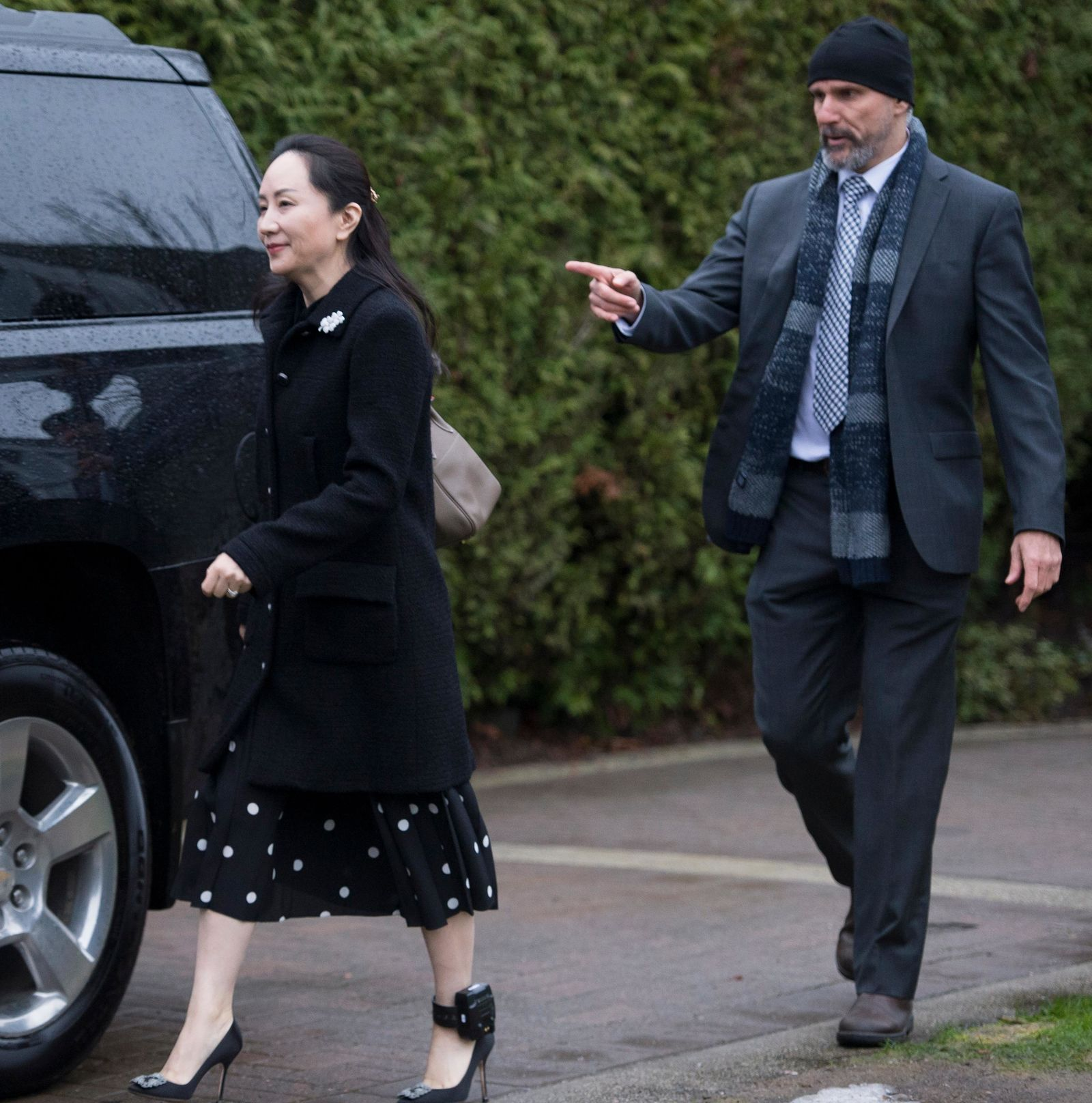 A security member points the way as Meng Wanzhou, chief financial officer of Huawei, leaves her home in Vancouver, Monday, January, 20, 2020. (Jonathan Hayward/The Canadian Press via AP)