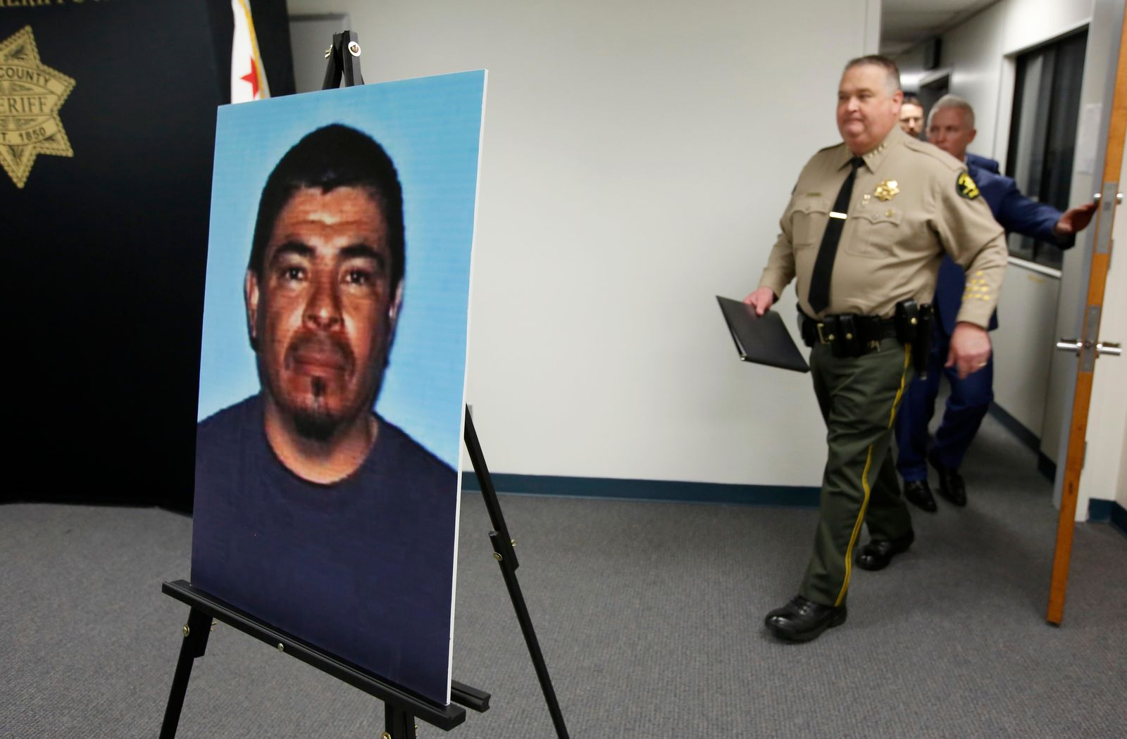 A photo of Paul Perez, who has been arrested in the deaths of his five children, is displayed as Yolo County Sheriff Tom Lopez, left and Yolo County District Attorney Jeff Reisig, right, enter a news conference in Woodland, Calif., Monday, Jan. 27, 2020. Paul Perez, 57, has been arrested in the decades-old killings of five of his infant children, a case the sheriff said had haunted his agency for years, the Yolo County Sheriff's Office said Monday, Jan. 27, 2020. (AP Photo/Rich Pedroncelli)