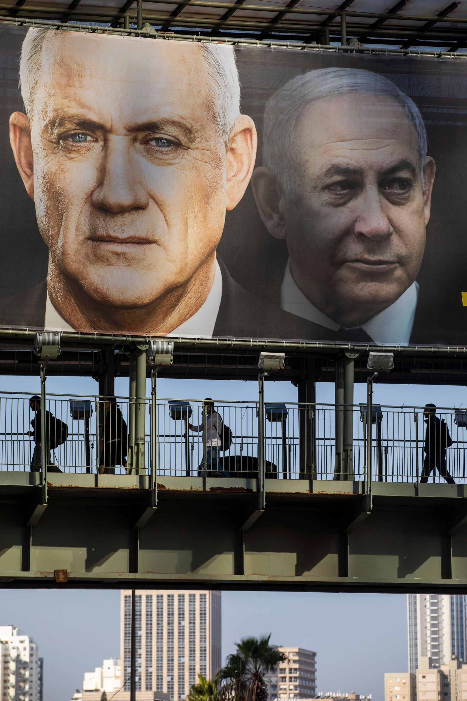 People walk on a bridge under an election campaign billboard of Blue and White party shows its party leader Benny Gantz, and Israeli Prime Minister Benjamin Netanyahu, in Ramat Gan, Israel, Tuesday, Feb. 18, 2020. (AP Photo/Oded Balilty)