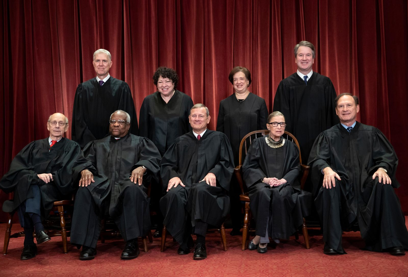 FILE - In this Nov. 30, 2018, file photo, the justices of the U.S. Supreme Court gather for a formal group portrait to include the new Associate Justice, top row, far right, at the Supreme Court Building in Washington. Seated from left: Associate Justice Stephen Breyer, Associate Justice Clarence Thomas, Chief Justice of the United States John G. Roberts, Associate Justice Ruth Bader Ginsburg and Associate Justice Samuel Alito Jr. Standing behind from left: Associate Justice Neil Gorsuch, Associate Justice Sonia Sotomayor, Associate Justice Elena Kagan and Associate Justice Brett M. Kavanaugh. (AP Photo/J. Scott Applewhite, File)