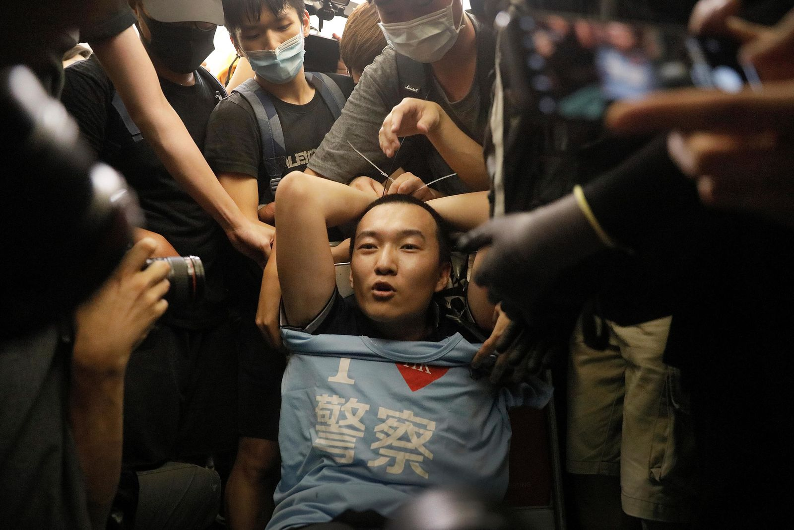 "Protesters surround a man carrying a t-shirt baring the words ""I love police"" who protesters claimed was a police officer from mainland China, during a demonstration at the Airport in Hong Kong, Tuesday, Aug. 13, 2019. Riot police clashed with pro-democracy protesters at Hong Kong's airport late Tuesday night, a chaotic end to a second day of demonstrations that caused mass flight cancellations at the Chinese city's busy transport hub. (AP Photo/Vincent Yu)"