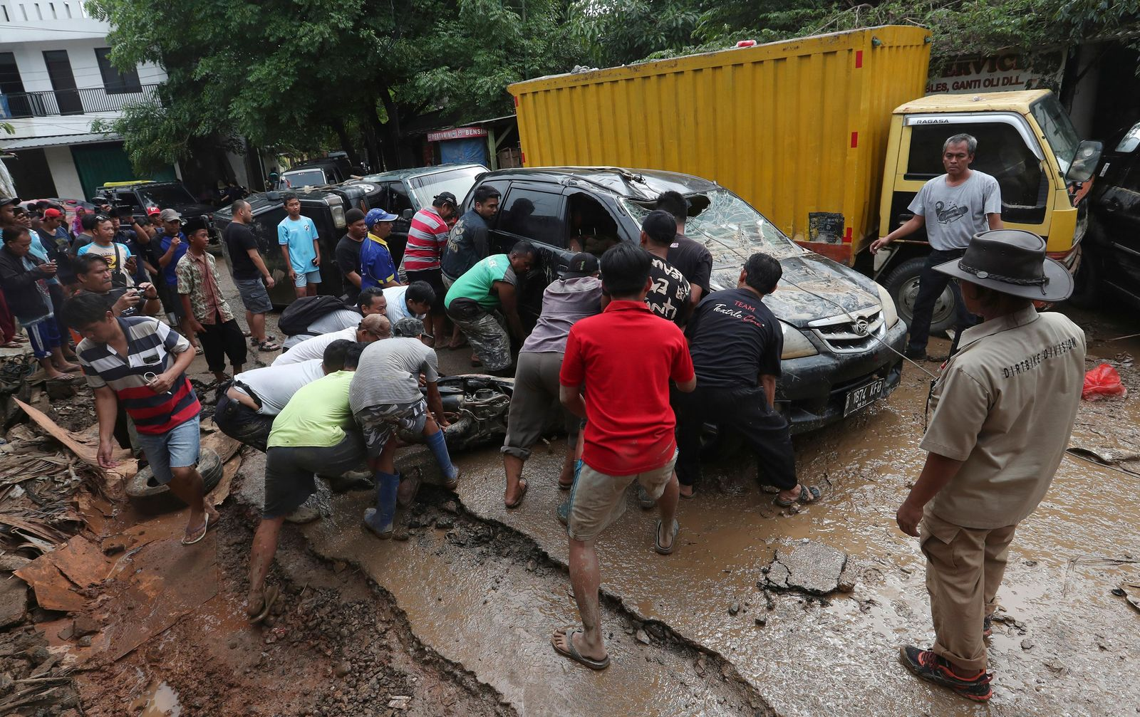 Residents try to move the wreckage of cars that were swept away by flood in Bekasi, West Java, Indonesia, Friday, Jan. 3, 2020. (AP Photo/Achmad Ibrahim)