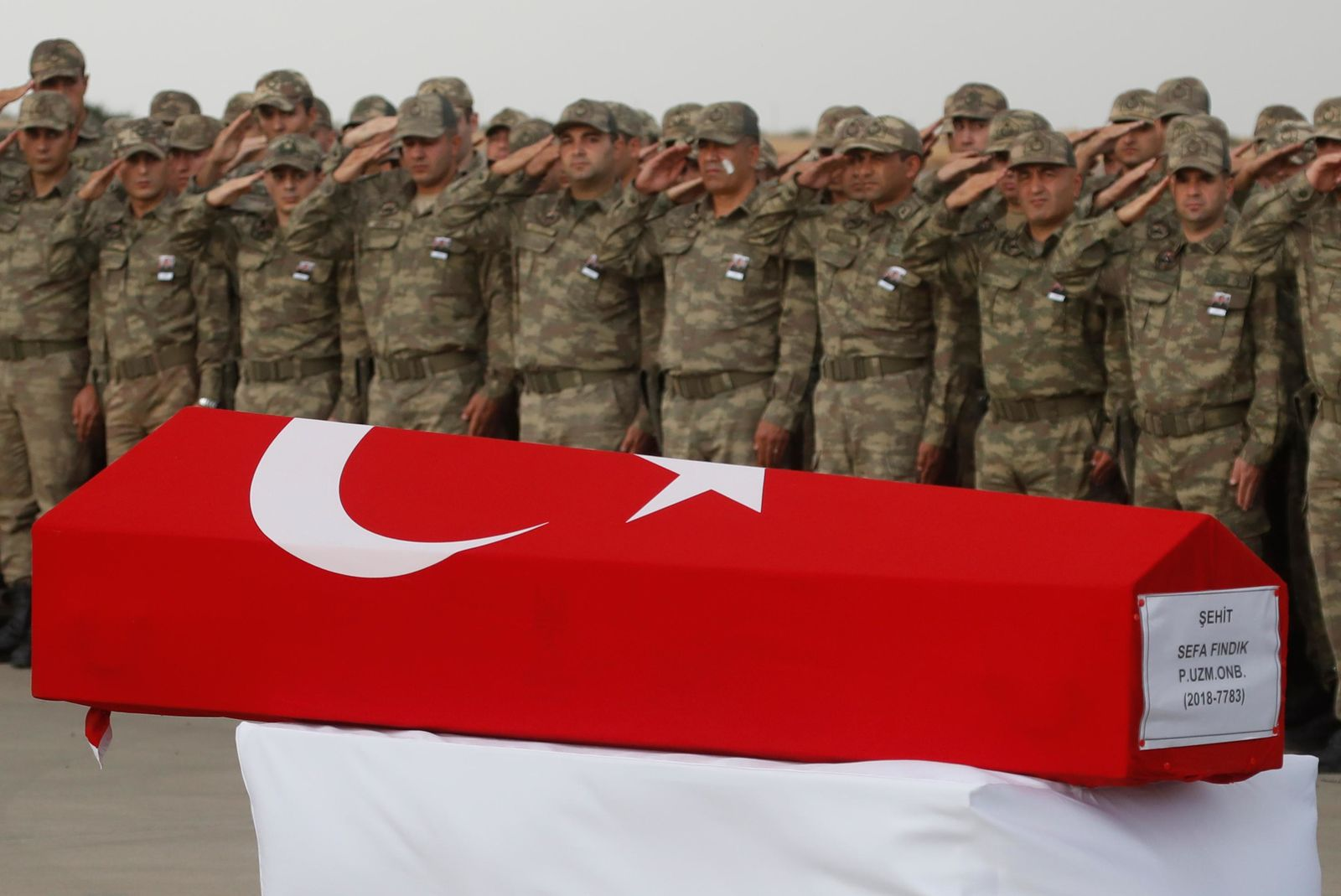 Turkish soldiers salute the Turkish flag-draped coffin of soldier Sefa Findik, killed in action in Syria earlier in the day, during a ceremony at the airport in Sanliurfa, southeastern Turkey, Sunday, Oct. 20, 2019.  This death brings Turkey's military death toll to seven soldiers in its wide-ranging offensive against Syrian Kurdish forces.(AP Photo/Lefteris Pitarakis)