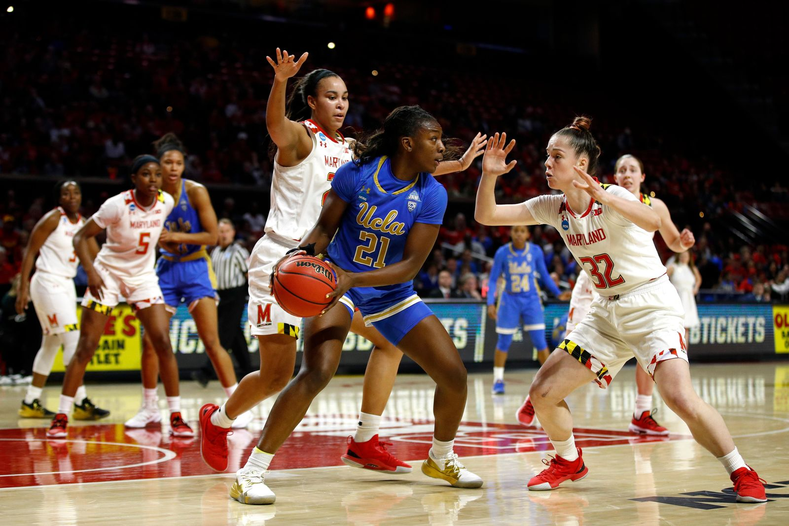 UCLA forward Michaela Onyenwere (21) protects the ball as she is pressured by Maryland guard Sara Vujacic, right, and forward Stephanie Jones during the first half of a second-round game in the NCAA women's college basketball tournament, Monday, March 25, 2019, in College Park, Md. (AP Photo/Patrick Semansky)