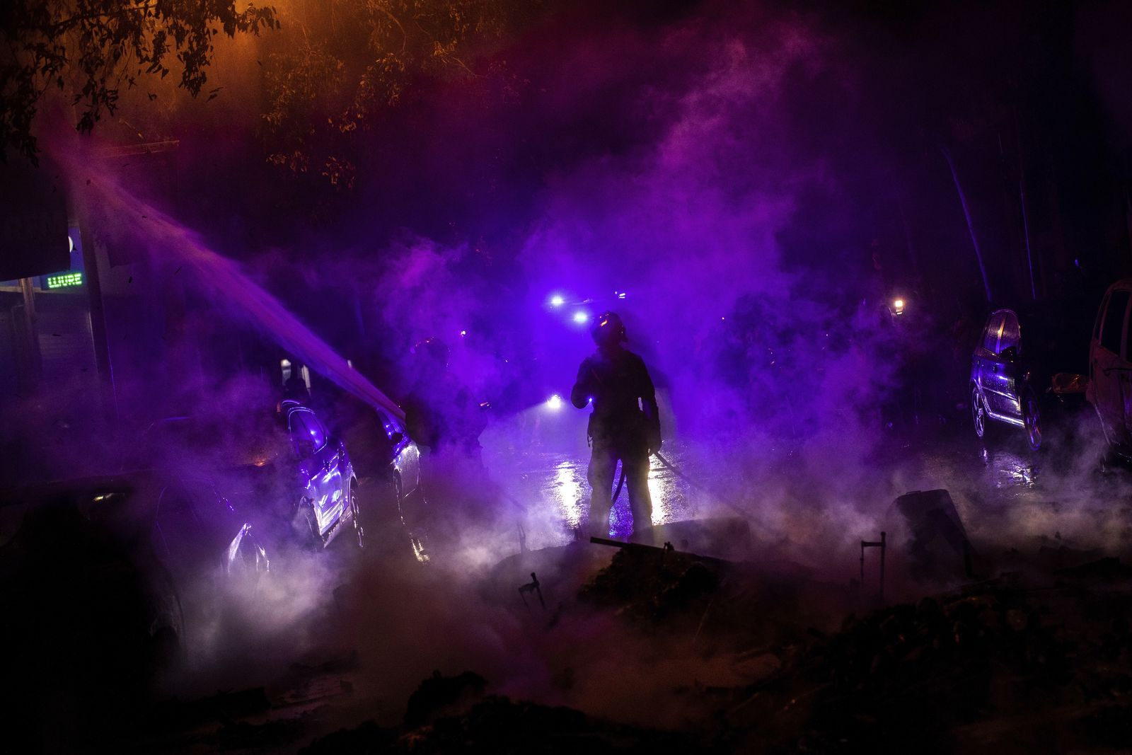 Firefighters try to put out fires on the street during clashes between protestors and police in Barcelona, Spain, Wednesday, Oct. 16, 2019.{ } (AP Photo/Bernat Armangue)