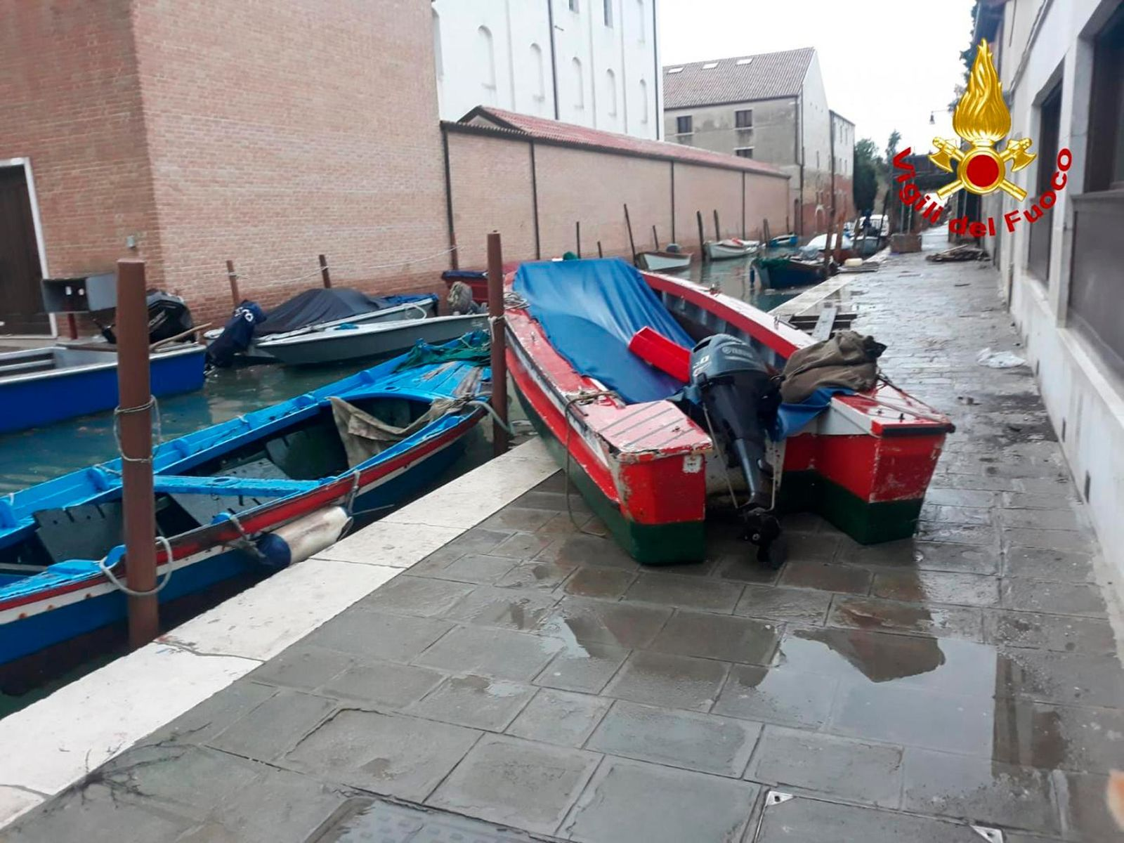 A stranded boat is seen on the dock after a high tide, in Venice, Italy, Wednesday, Nov. 13, 2019. (Italian Firefighters Vigili del Fuoco via AP)