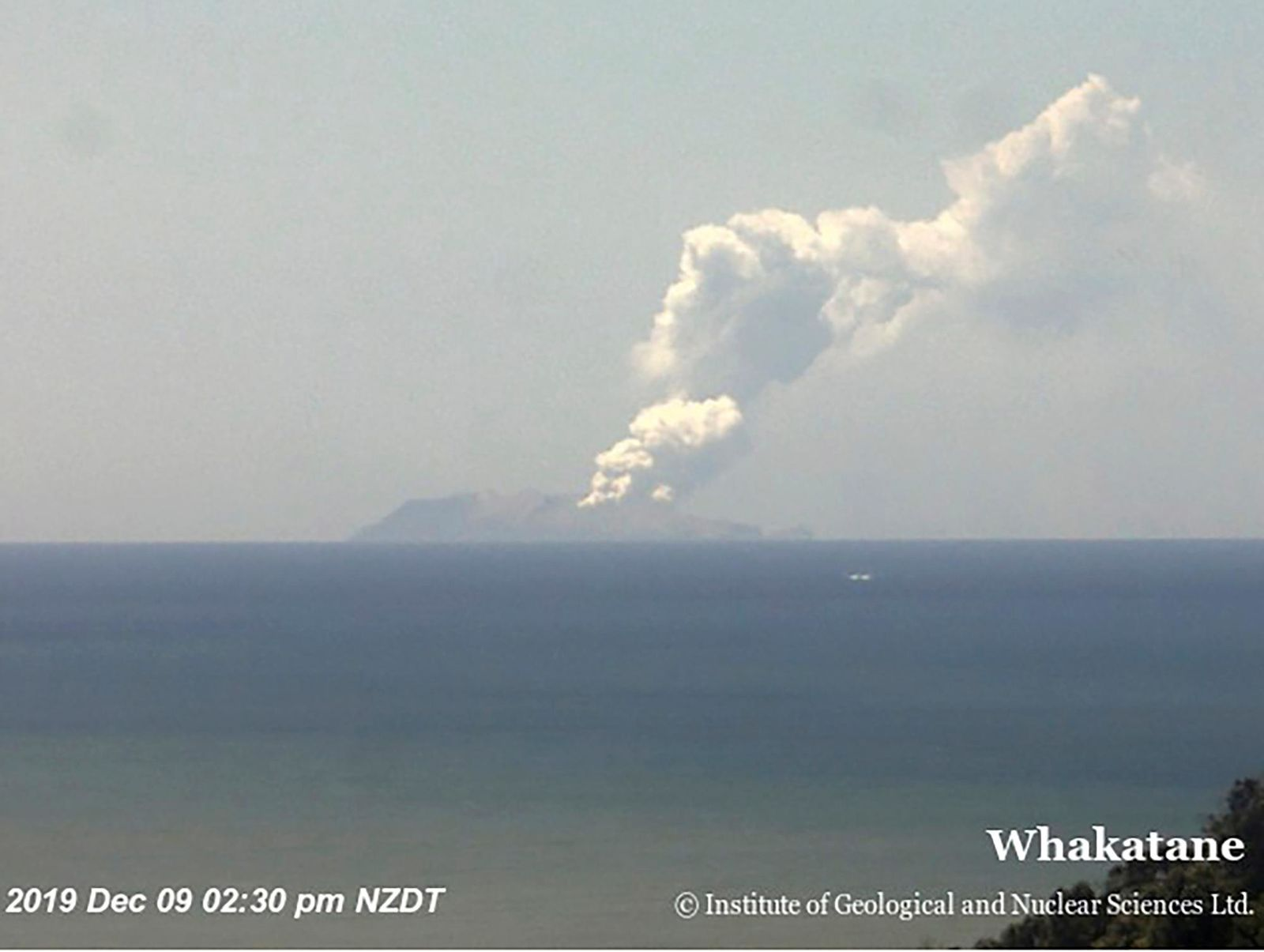 This image released by GNS Science, shows plumes of smoke from a volcanic eruption on White Island, seen from Whakatane, New Zealand Monday, Dec. 9, 2019. (GNS Science via AP)