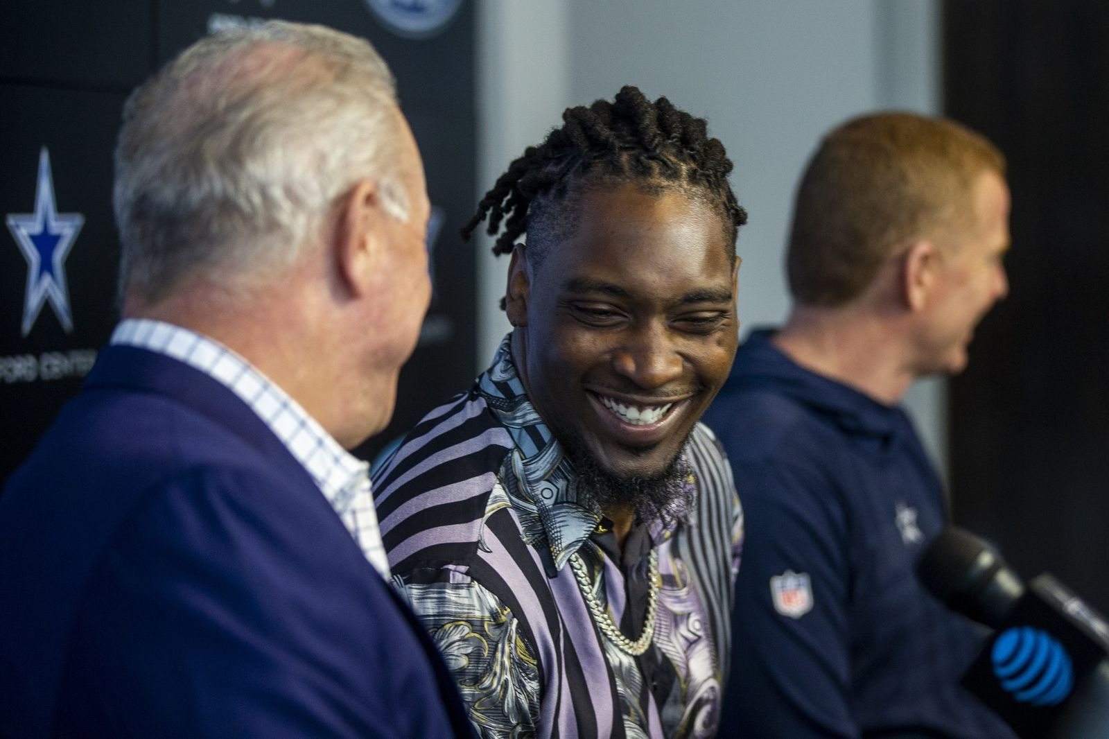 Dallas Cowboys CEO Stephen Jones, left, shares a moment with defensive end Demarcus Lawrence as Cowboys owner Jerry Jones gives remarks during a press conference at The Star in Frisco, Texas, Tuesday, April 9, 2019. DeMarcus Lawrence may not be the highest-paid Dallas Cowboys player in history for long. It doesn't mean the club's best defensive end can't enjoy the distinction while it lasts. The 26-year-old Lawrence signed a $105 million, five-year contract Tuesday.(Shaban Athuman/The Dallas Morning News via AP)
