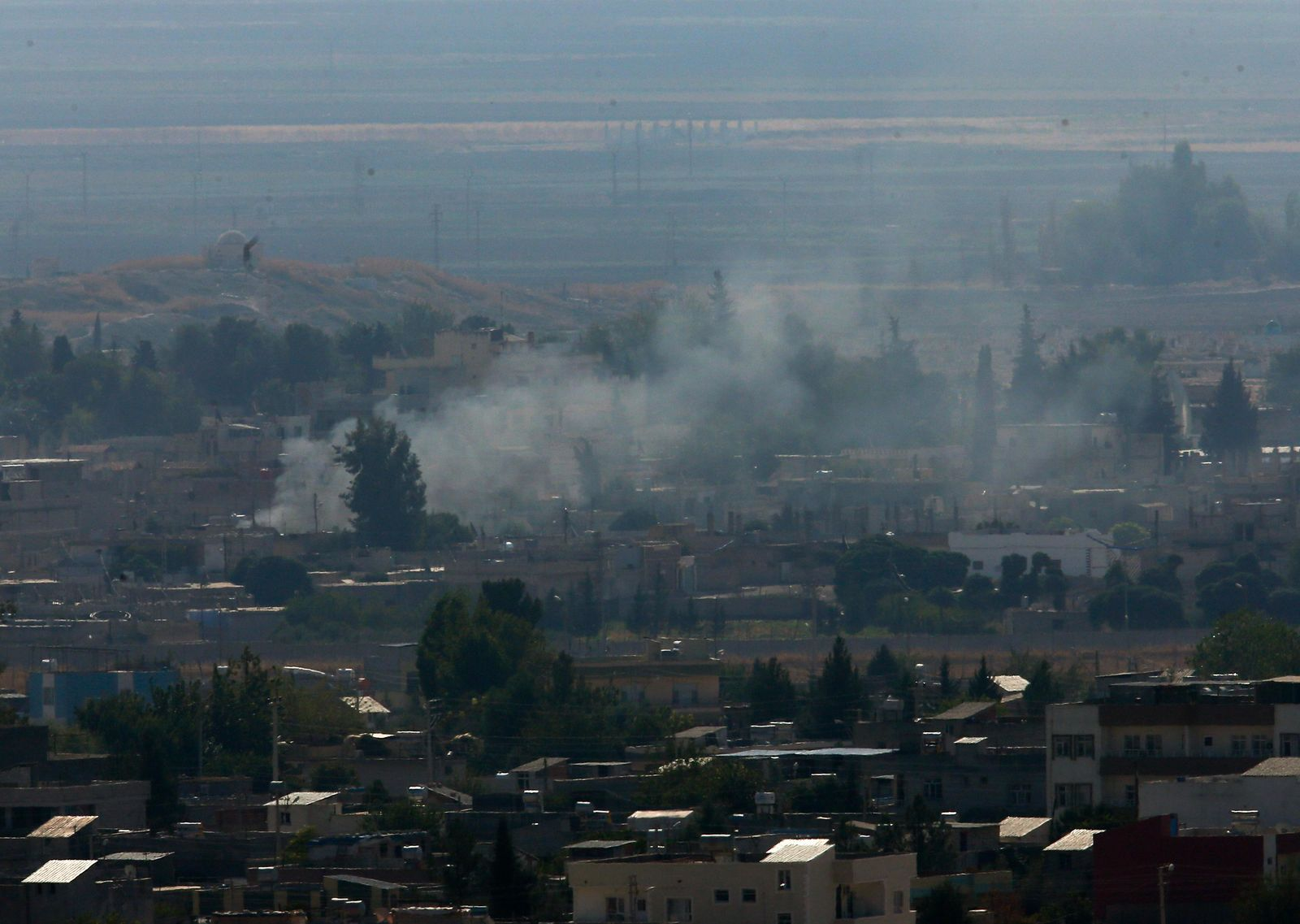 In this photo taken from the Turkish side of the border between Turkey and Syria, in Ceylanpinar, Sanliurfa province, southeastern Turkey, smoke billows from targets in Ras al-Ayn, Syria, caused by shelling by Turkish forces, Friday, Oct. 18, 2019.{ } (AP Photo/Lefteris Pitarakis)