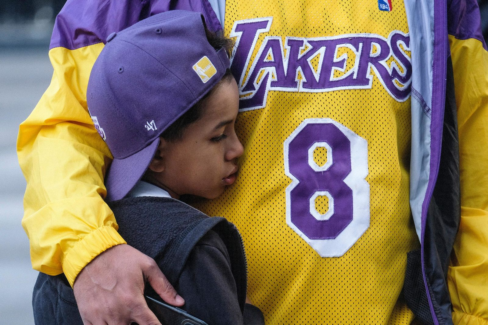 Eric Mascarenhas comforts his son Nicolas at a memorial for Kobe Bryant near Staples Center Monday, Jan. 27, 2020, in Los Angeles. Bryant, the 18-time NBA All-Star who won five championships and became one of the greatest basketball players of his generation during a 20-year career with the Los Angeles Lakers, died in a helicopter crash Sunday. (AP Photo/Ringo H.W. Chiu)