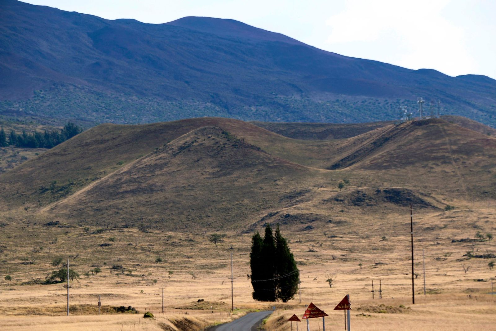 This photo provided by the Hawaii Department of Land and Natural Resources (DLNR) shows the road to Mauna Kea, a mountain considered sacred by some Native Hawaiians, in the distance, free of traffic as protesters continued to block the roadway for the fourth day Thursday, July 18, 2019. The action Thursday comes a day after 33 people were arrested, many of them elderly. Activists have fought the $1.4 billion Thirty Meter Telescope in courts and on the streets for years, but the latest protest could be their final stand as they run out of legal options. (Hawaii DLNR via AP)