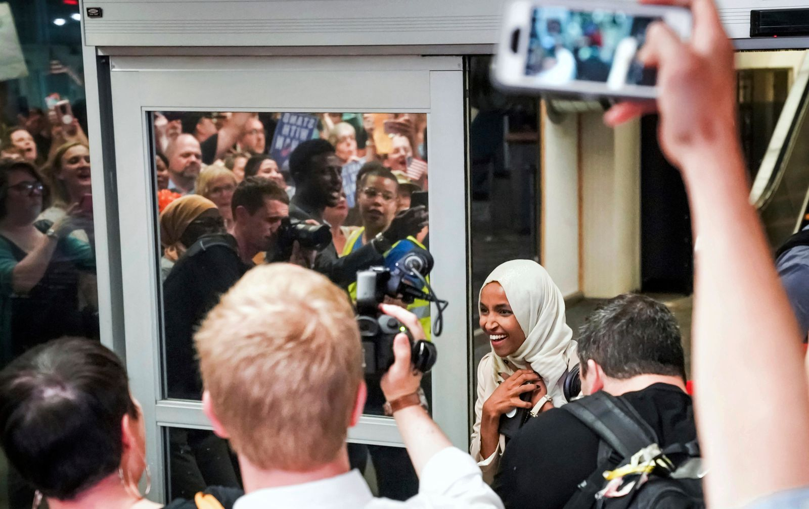 "U.S. Rep. Ilhan Omar reacts as she's greeted by supporters cheering ""Welcome Home Ilhan!"" as she arrived home at Minneapolis–Saint Paul International Airport, Thursday, July 18, 2019, in Minnesota. (Glen Stubbe/Star Tribune via AP)"
