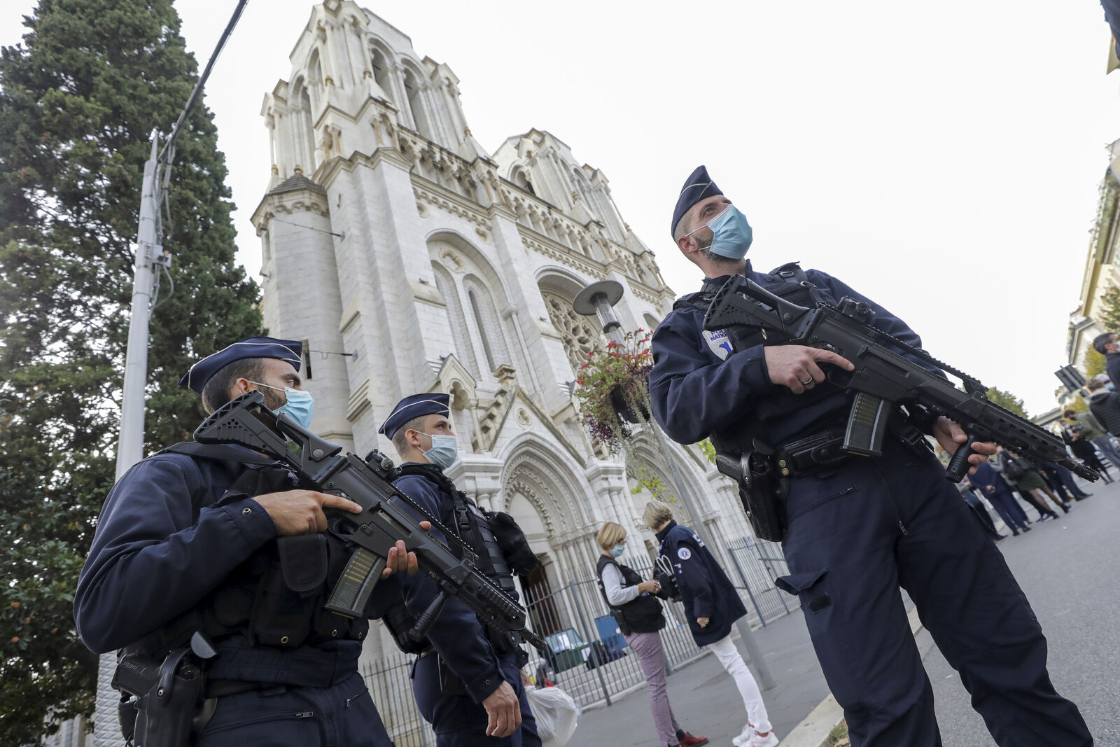 FILE- French police officers stand near Notre Dame church in Nice, southern France, Thursday, Oct. 29, 2020.{ } (Eric Gaillard/Pool via AP)