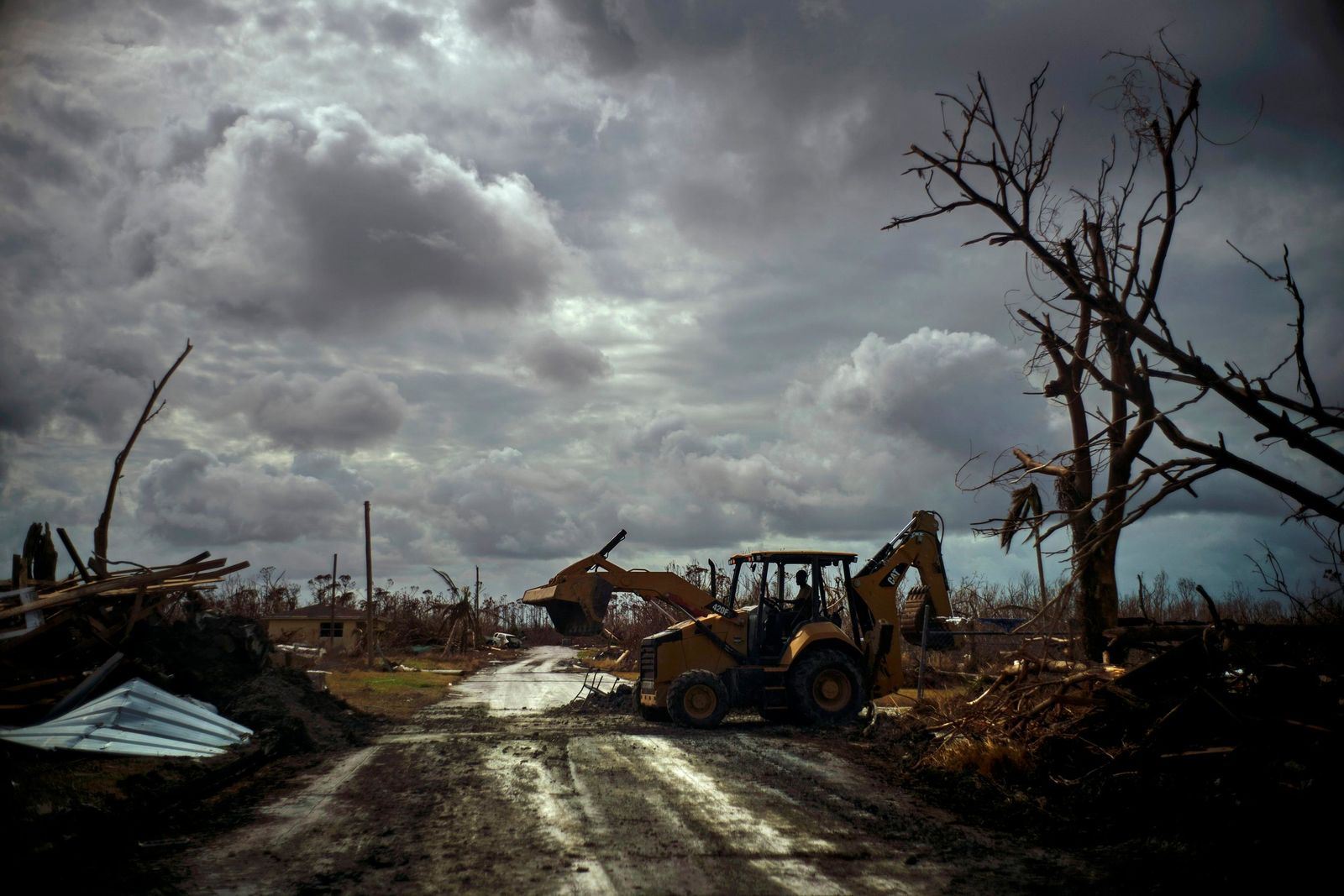 Mos Antenor, 42, drives a bulldozer while clearing the road after Hurricane Dorian Mclean's Town, Grand Bahama, Bahamas, Friday Sept. 13, 2019. (AP Photo/Ramon Espinosa)