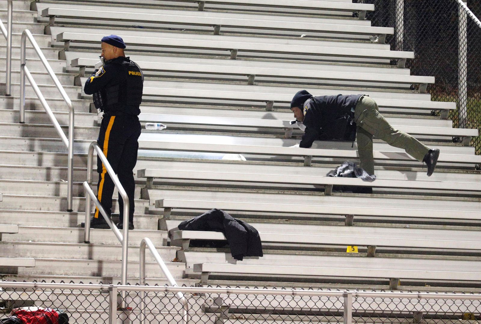 Pleasantville police search the stands after a shooting during a football game at Pleasantville High School in Pleasantville, N.J., Friday, Nov. 15, 2019. Players and spectators ran for cover Friday night when a gunman opened fire at the New Jersey high school football game. (Edward Lea/The Press of Atlantic City via AP)