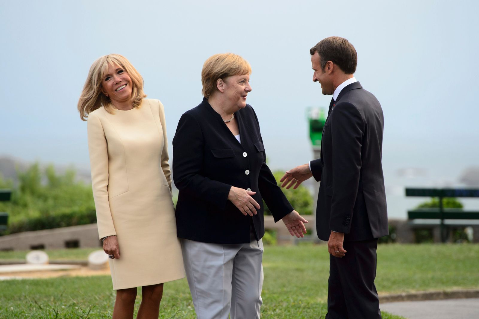 German Chancellor Angela Merkel, center, is greeted by President of France Emmanuel Macron, right, and wife Brigitte Macron as he arrives to the G7 Summit in Biarritz, France, Saturday, Aug. 24, 2019. (Sean Kilpatrick/The Canadian Press via AP)