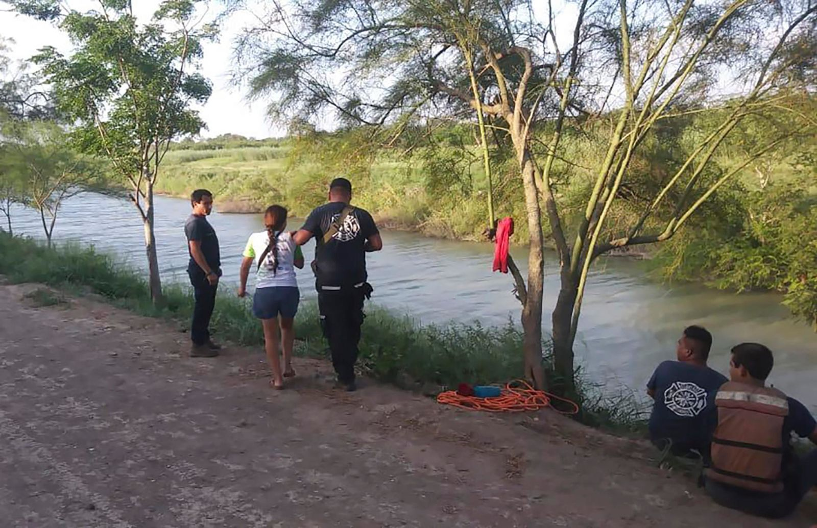 Tania Vanessa Ávalos of El Salvador, center left, is assisted by Mexican authorities after her husband and nearly two-year-old daughter were swept away by the current while trying to cross the Rio Grande to Brownsville, Texas, in Matamoros, Mexico, Sunday, June 23, 2019. Their bodies, the toddler still tucked into her father's shirt with her arm loosely draped around him, were discovered Monday morning several hundred yards from where they had tried to cross. (AP Photo/Julia Le Duc)