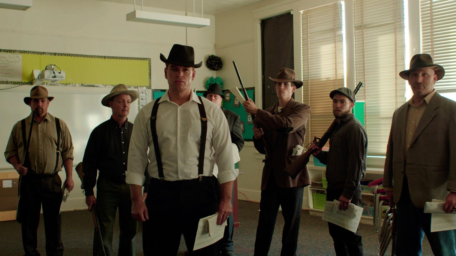 "This undated photo provided by 4th Row Films, town residents dressed in period costume stand in a modern day classroom in ""Bisbee '17,"" as they re-enact the deputizing of a private police force that broke up a brewing strike at a copper mine on July 12, 1917 when they rounded up some 1,200 miners, locked them into cattle cars and deported them over the state line into a barren part of southern New Mexico. (Jarred Alterman/4th Row Films via AP)"