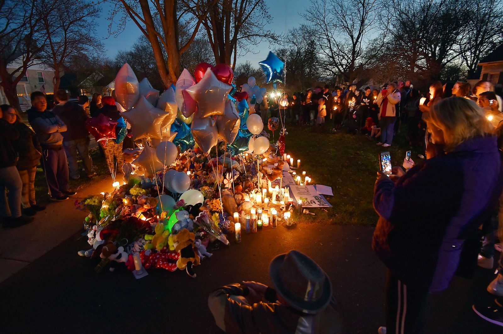 "In this Wednesday, April 24, 2019 photo, community members in Crystal lake, Ill. hold a vigil in memory of 5-year-old Andrew ""AJ"" Freund. Authorities searching for the missing Illinois boy who had lived in deplorable conditions dug up his body Wednesday and charged his parents with murder, sadly declaring that the youngster would ""no longer have to suffer.""  (John Starks/Daily Herald via AP)"