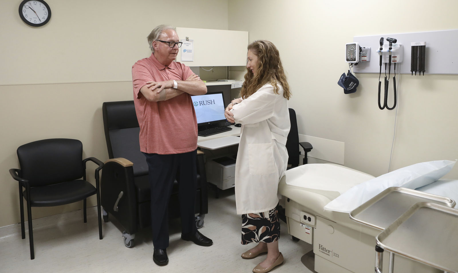 In this July 9, 2019 photo, Dr. Jori Fleisher, neurologist, examines Thomas Doyle, 66, at the Rush University Medical Center in Chicago. Doyle, 66, hopes blood tests may someday replace the invasive diagnostic testing he endured to be diagnosed 4.5 years ago with Lewy body dementia. (AP Photo/Teresa Crawford)