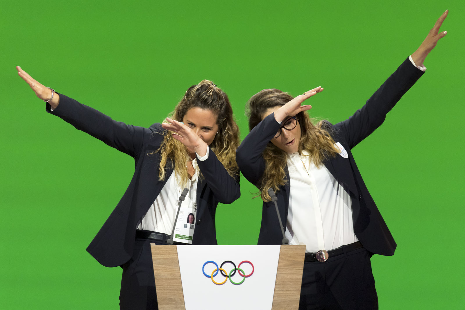 Italian snowboarder Michela Moioli, left, and Italian skier Sofia Goggia, right, dab after speaking during the presentation final presentation of the Milan-Cortina candidate cities the first day of the 134th Session of the International Olympic Committee (IOC), at the SwissTech Convention Centre, in Lausanne, Switzerland, Monday, June 24, 2019. (Laurent Gillieron/Keystone via AP)