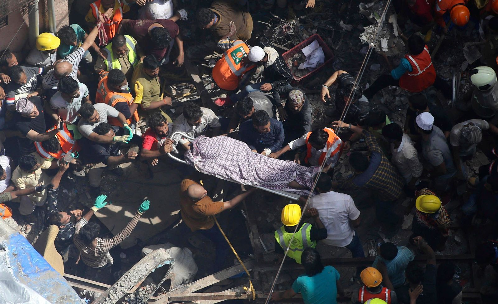Rescuers carry the body of a victim at the site of a building that collapsed in Mumbai, India, Tuesday, July 16, 2019.{ } (AP Photo/Rajanish Kakade)