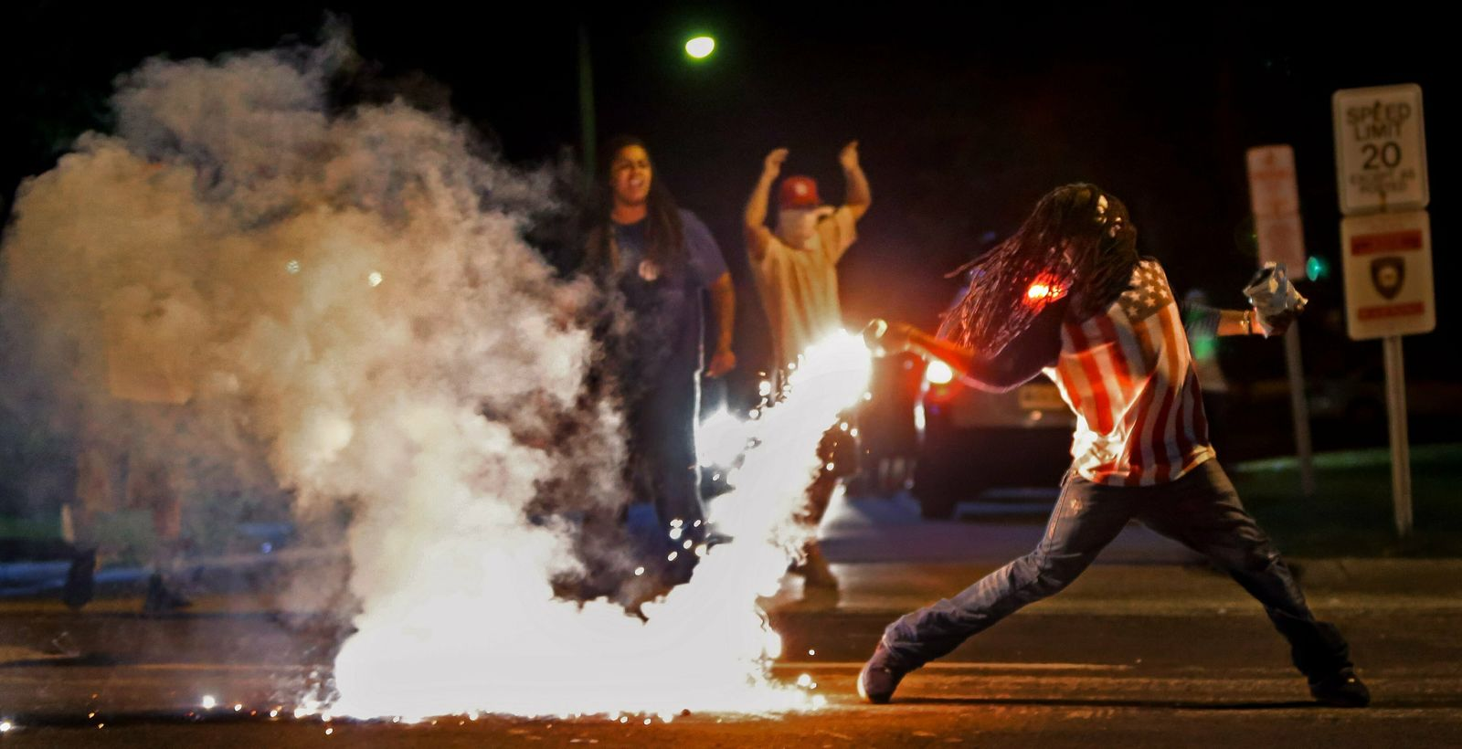 FILE - In this Aug. 13, 2014, file photo Edward Crawford Jr., returns a tear gas canister fired by police who were trying to disperse protesters in Ferguson, Mo. . (Robert Cohen/St. Louis Post-Dispatch via AP, File)