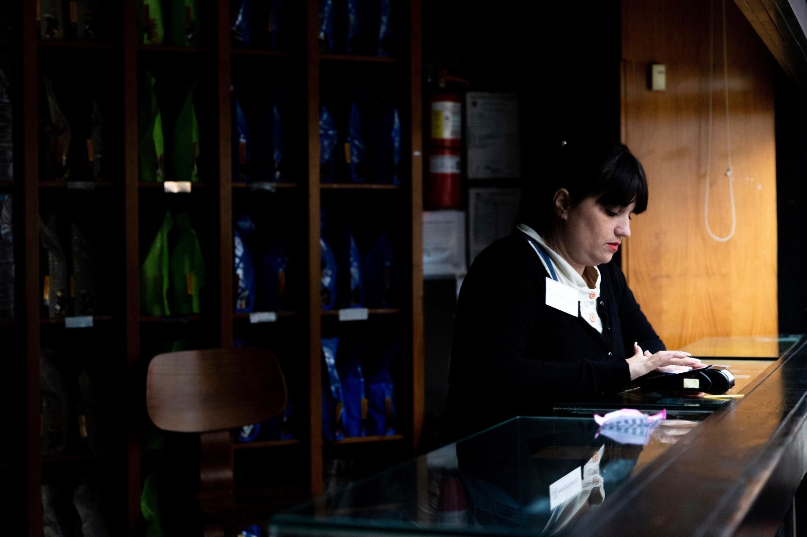 An employee uses a payment device in a coffee shop still affected by the power outage, in Buenos Aires, Argentina, Monday, June 17, 2019. As lights turned back on across Argentina, Uruguay and Paraguay after a massive blackout that hit tens of millions people, authorities were still largely in the dark about what caused the collapse of the interconnected grid and were tallying the damage from the unforeseen disaster. (AP Photo/Tomas F. Cuesta)
