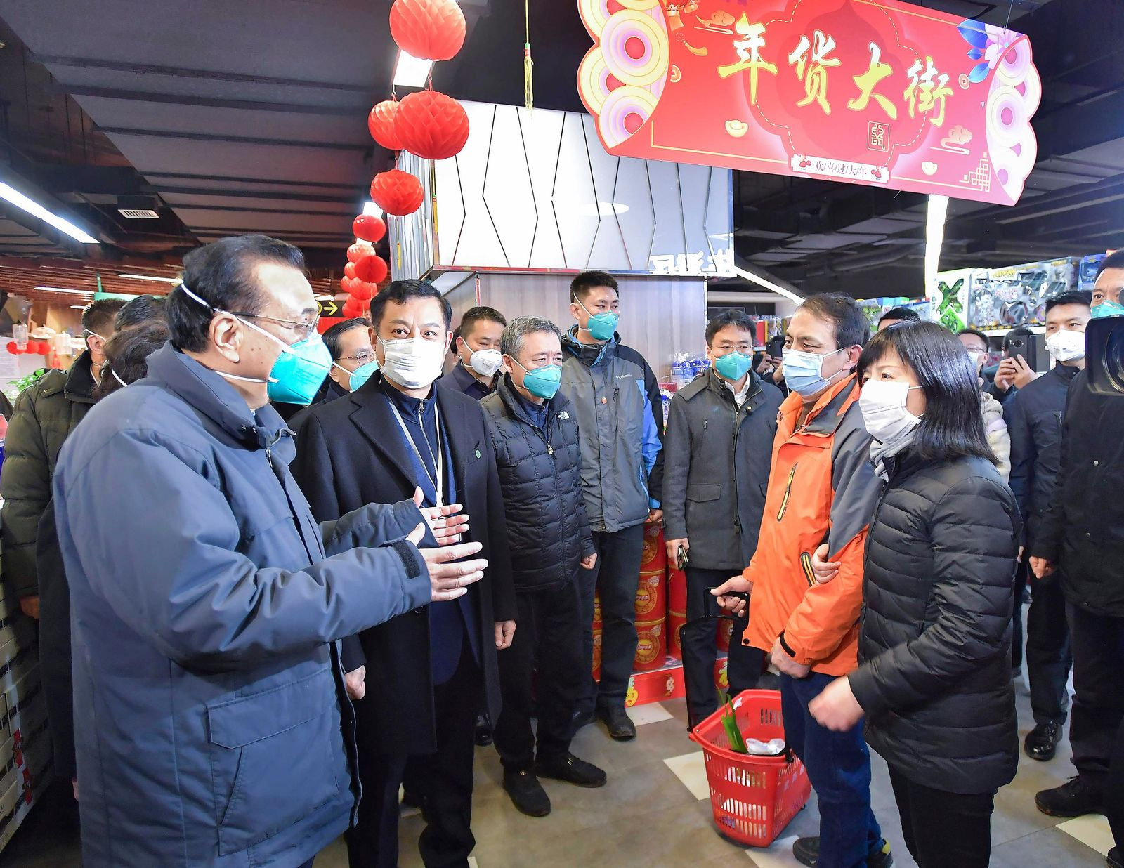 In this photo released by China's Xinhua News Agency, Chinese Premier Li Keqiang, left, speaks with people at a supermarket in Wuhan in central China's Hubei province, Monday, Jan. 27, 2020. China on Monday expanded its sweeping efforts to contain a deadly virus, extending the Lunar New Year holiday to keep the public at home and avoid spreading infection. (Li Tao/Xinhua via AP)