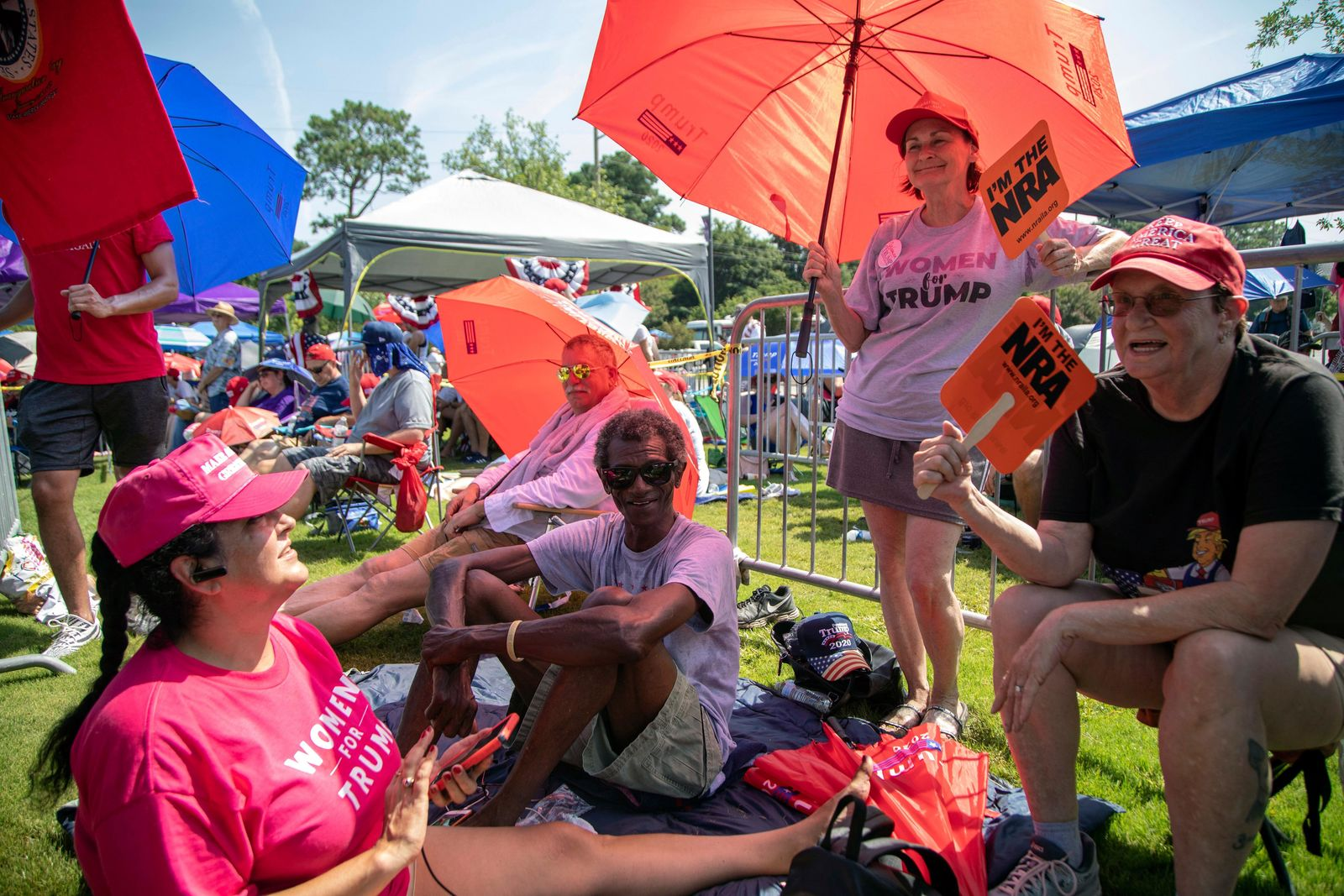 Foreground from left, Rosealinda Dorris, Michael Rountree, Maureen Fuster and Colleen Filo, all from Virginia Beach, Va., wait in line to see President Donald Trump, Wednesday morning, July 17, 2019 prior to a campaign rally at East Carolina University in Greenville, NC.(Travis Long/The News & Observer via AP)