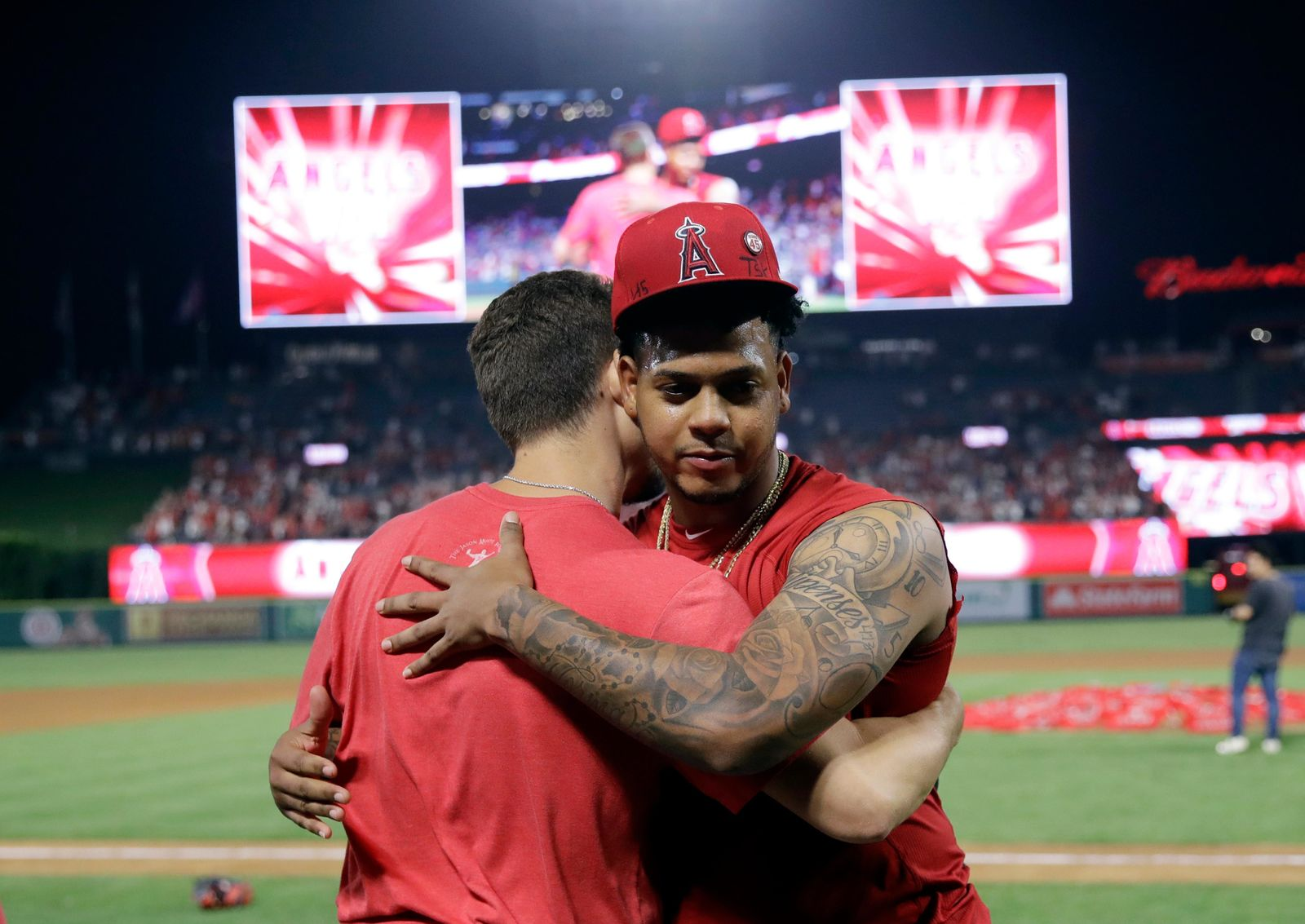 Los Angeles Angels relief pitcher Felix Pena, right, hugs starter Taylor Cole after they threw a combined-no hitter against the Seattle Mariners during a baseball game Friday, July 12, 2019, in Anaheim, Calif. The Angels won 13-0. (AP Photo/Marcio Jose Sanchez)