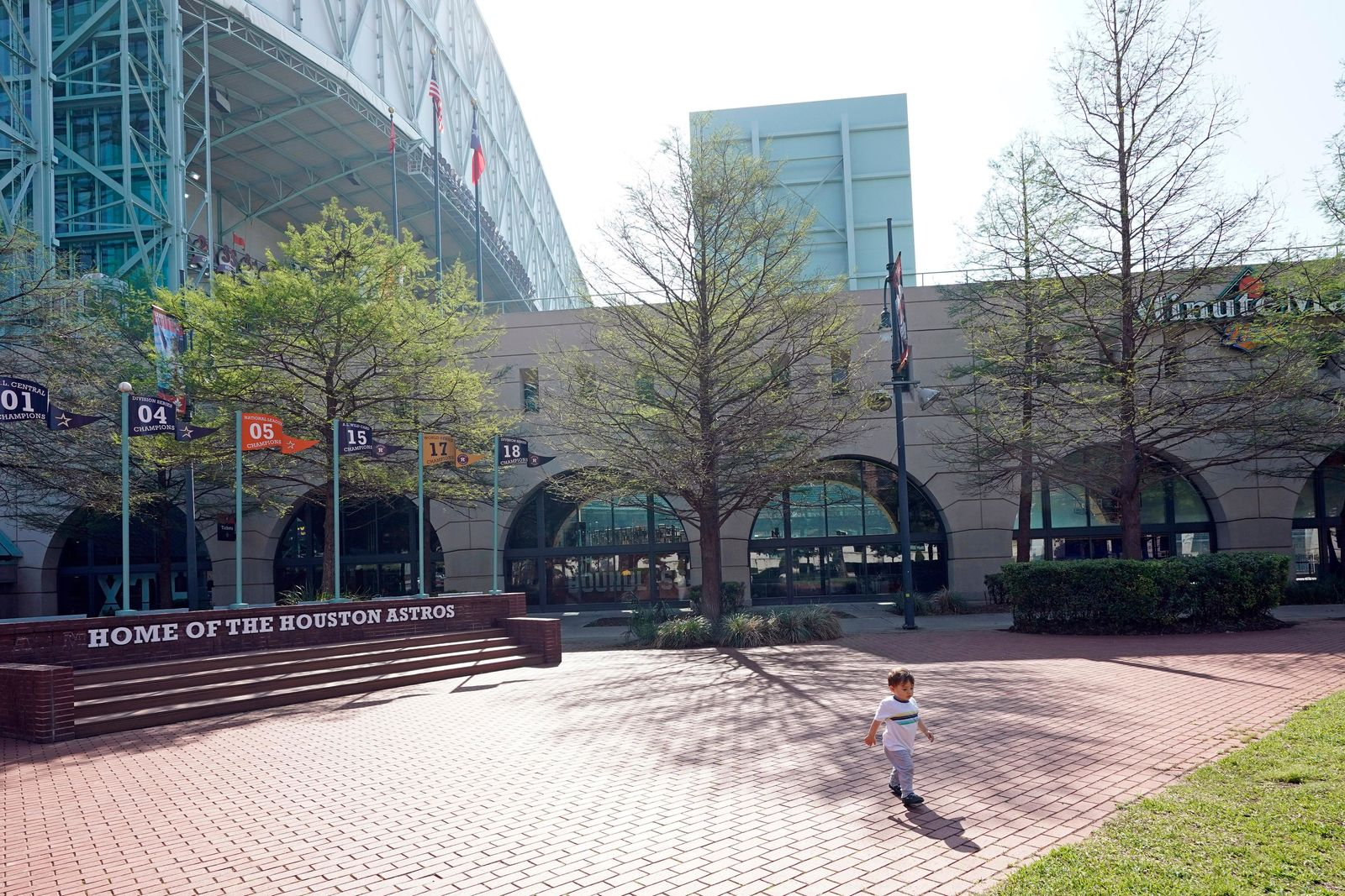 Lucas Estebanez, 18-months-old, runs outside Minute Maid Park Wednesday, March 25, 2020, in Houston. The Houston Astros would have hosted the Los Angeles Angels in their season-opening baseball game Thursday. The start of the regular season is indefinitely on hold because of the coronavirus pandemic. (AP Photo/David J. Phillip)